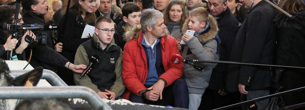 Head of France's rightwing Republicans opposition party Laurent Wauquiez (C, in red) visits the 55th International Agriculture Fair (Salon de l'Agriculture) at the Porte de Versailles exhibition center on February 27, 2018 in Paris.