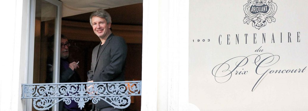 French writer Eric Vuillard smiles at the press from a balcony at the restaurant Drouant in Paris, France on November 6, 2017. Earlier in the day, Vuillard was awarded the Prix Goncourt for his novel 'L'Ordre du Jour', or 'The Agenda'.