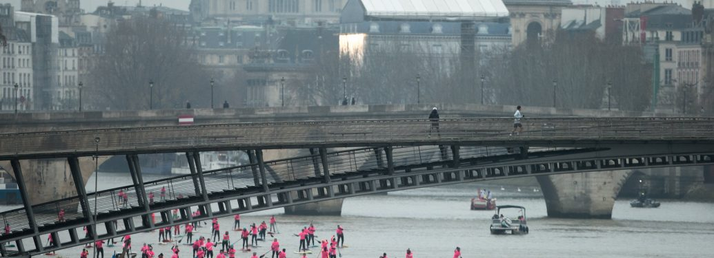 Paddle boarders pass near the Léopold Sedar Senghor bridge as they participate in the morning light in the Nautic SUP Paris crossing on the river Seine on December 3, 2017 in Paris. The Nautic SUP Paris crossing is the biggest Stand Up Paddle race in the