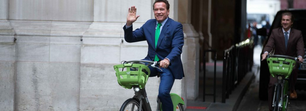Former Governor of the US State of California Arnold Schwarzenegger (C) waves as he rides a bicycle in Paris on December 11, 2017, on the sidelines of meetings with Mayor of Paris Anne Hidalgo.