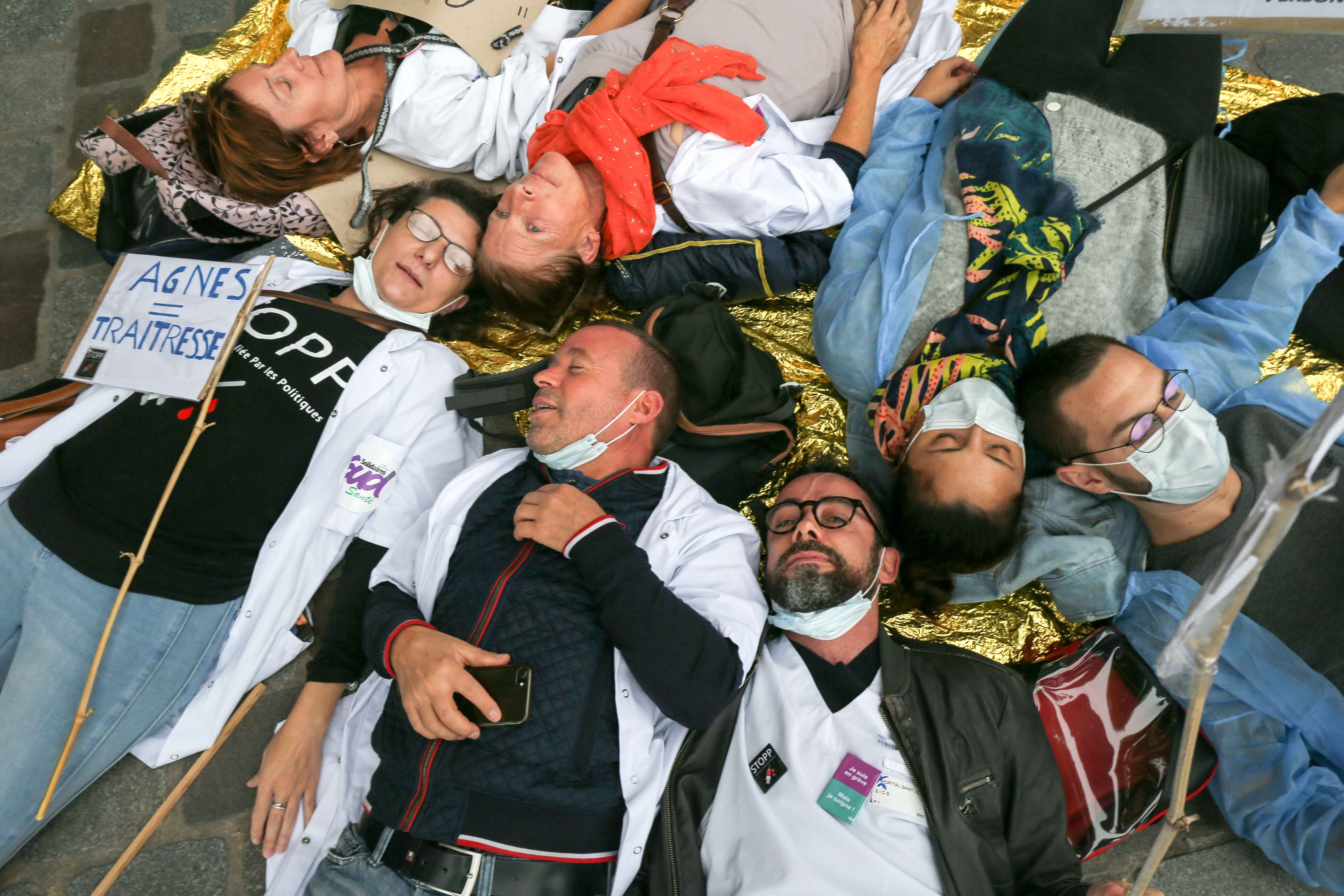 Doctors, nurses and cargivers make a die-in in Paris in front the Hotel de Ville, outside the headquarter of Assistance publique and Hôpitaux de Paris or AP-HP, public hospital system of Paris, to improve the working conditions in the French emergencies s
