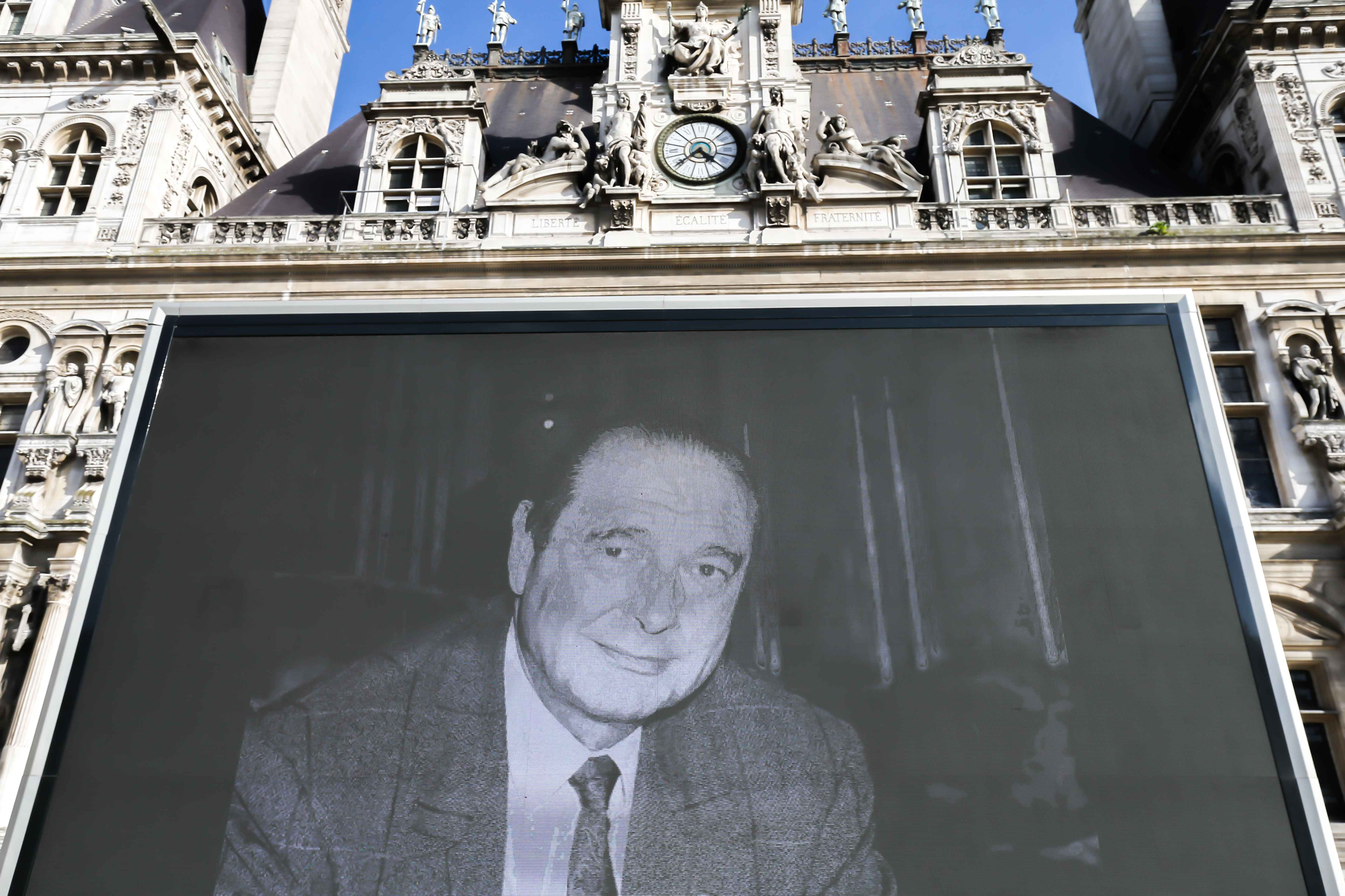 A giant screen displays photos in homage to late former French President Jacques Chirac in front of the City Hall square of Paris on September 28, 2019. Former French president Jacques Chirac died on September 26 at the age of 86 after a long battle with d