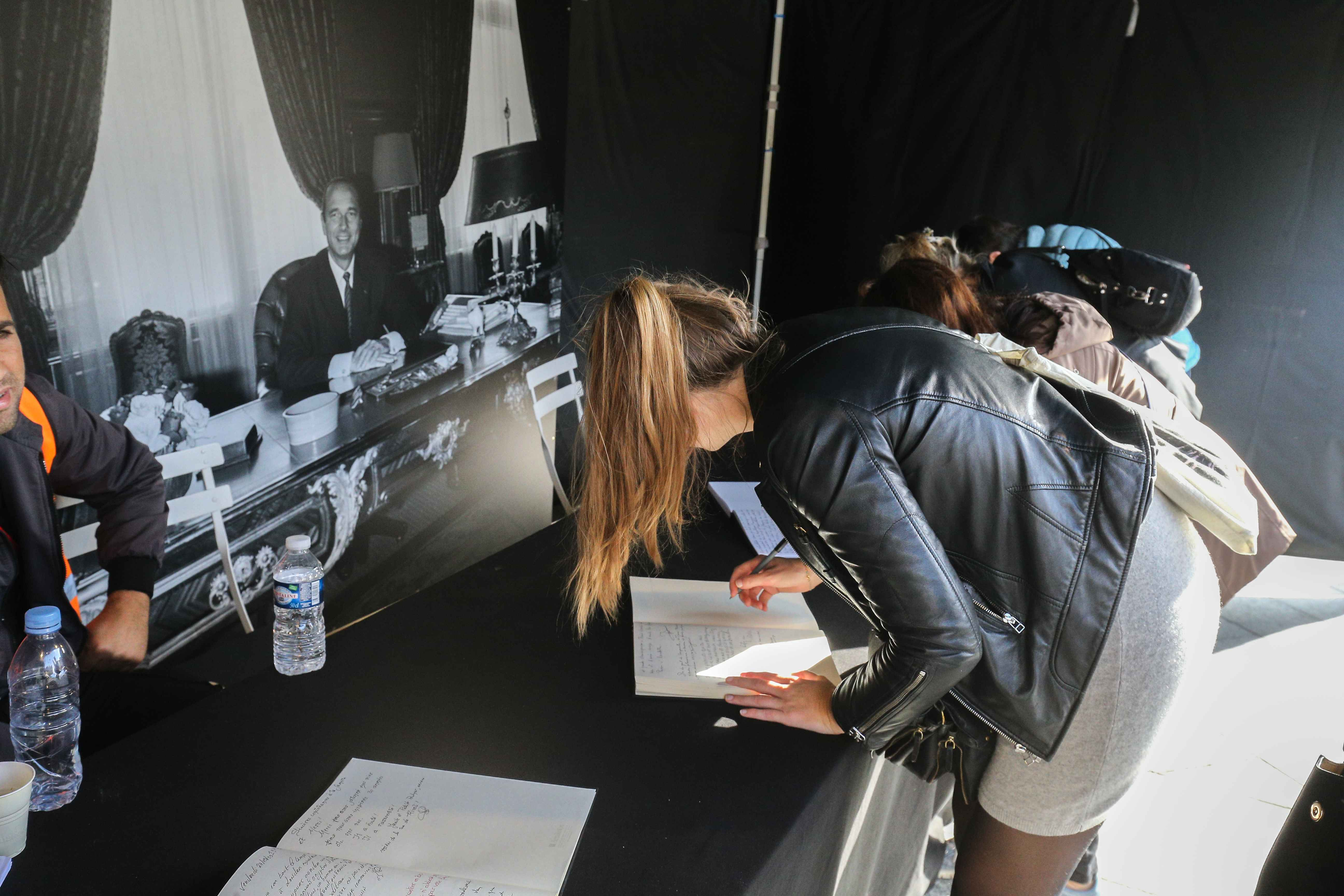 A woman signs a condolence register for late former French President Jacques Chirac in front of the City Hall square of Paris on September 28, 2019. Former French president Jacques Chirac died on September 26 at the age of 86 after a long battle with deter