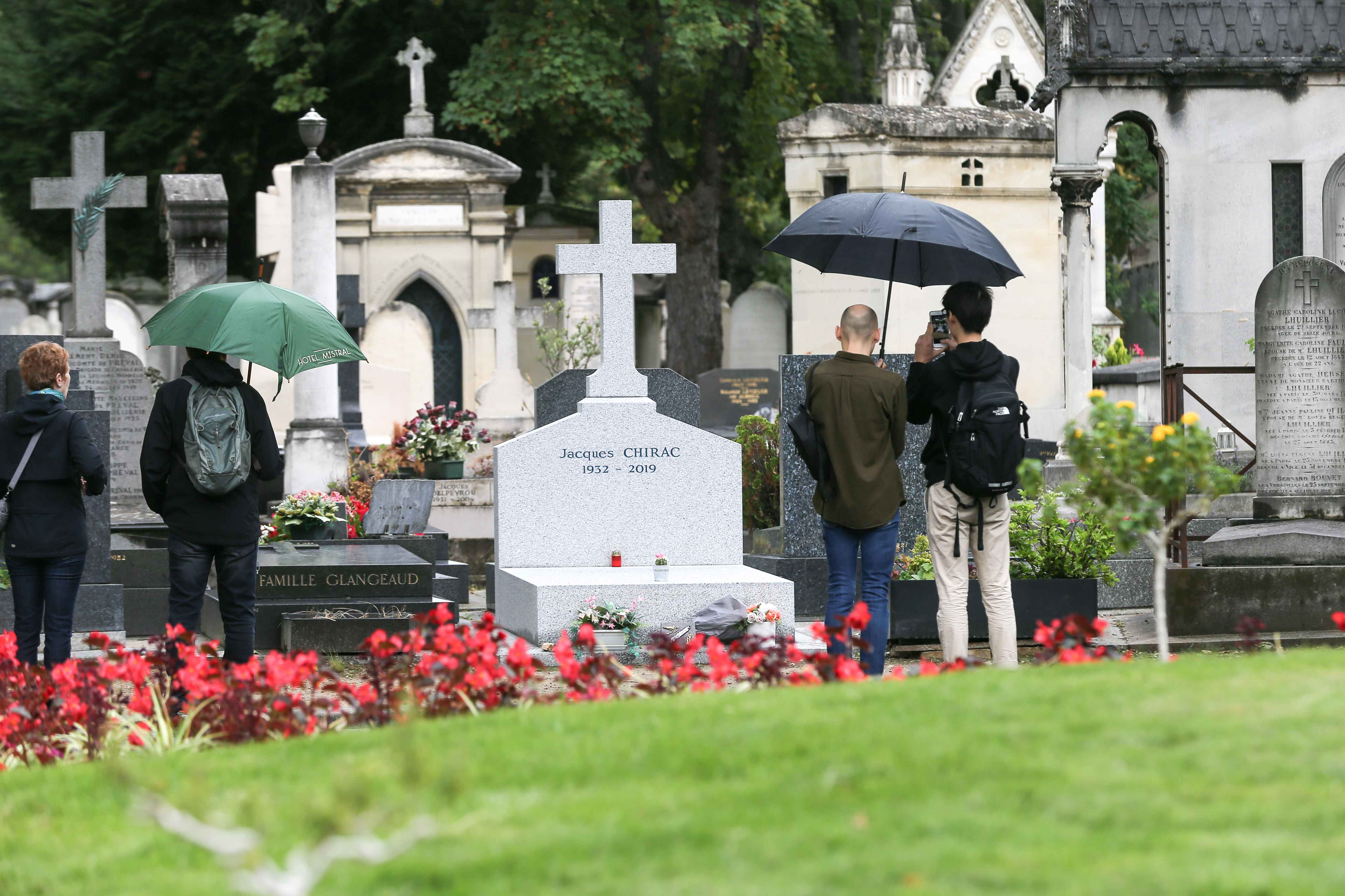 Bystanders gather beside the gravestone at The Montparnasse Cemetery in Paris on September 29, 2019, where former French President Jacques Chirac will be buried next to his daughter Laurence after his funeral which is scheduled for September 30. Jacques Ch