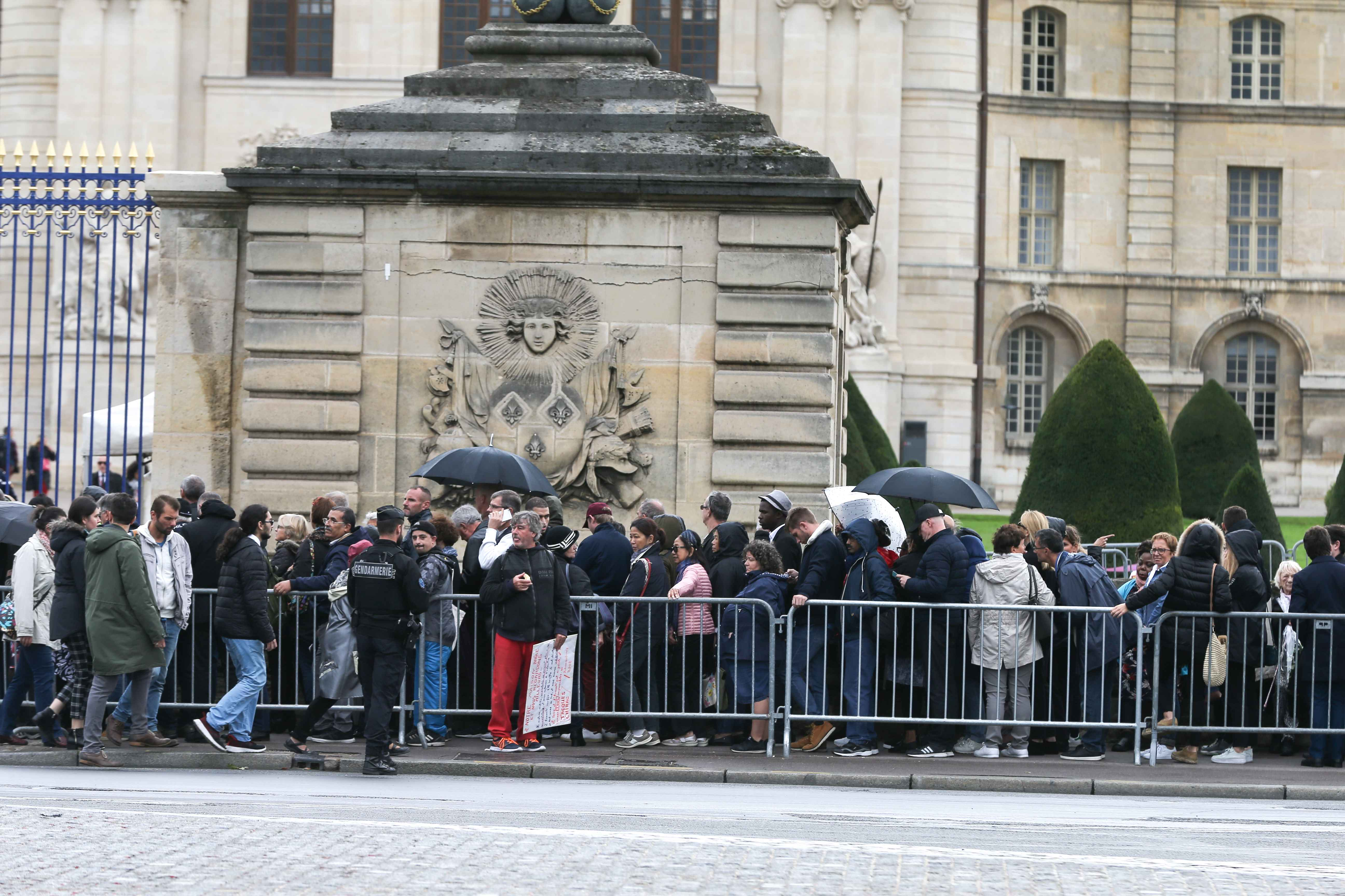 People wait to attend a public ceremony in homage to former French President Jacques Chirac outside the Saint-Louis-des-Invalides Cathedral in Paris on September 29, 2019. Jacques Chirac died on September 26 at the age of 86 after a long battle with deteri