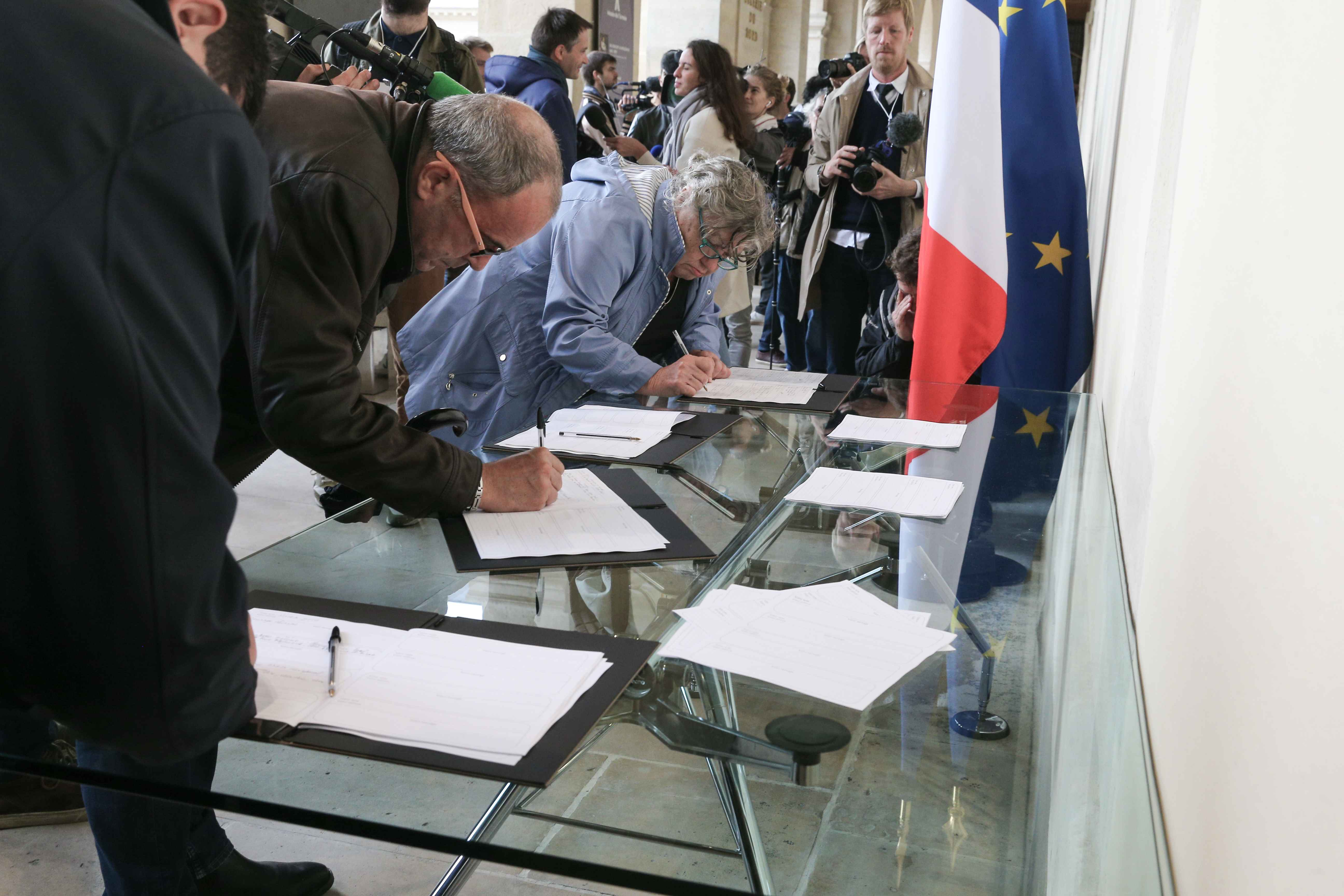 People sign condolence registers for late former French President Jacques Chirac at the Invalides memorial complex in central Paris on September 29, 2019. Jacques Chirac died on September 26 at the age of 86 after a long battle with deteriorating health, p