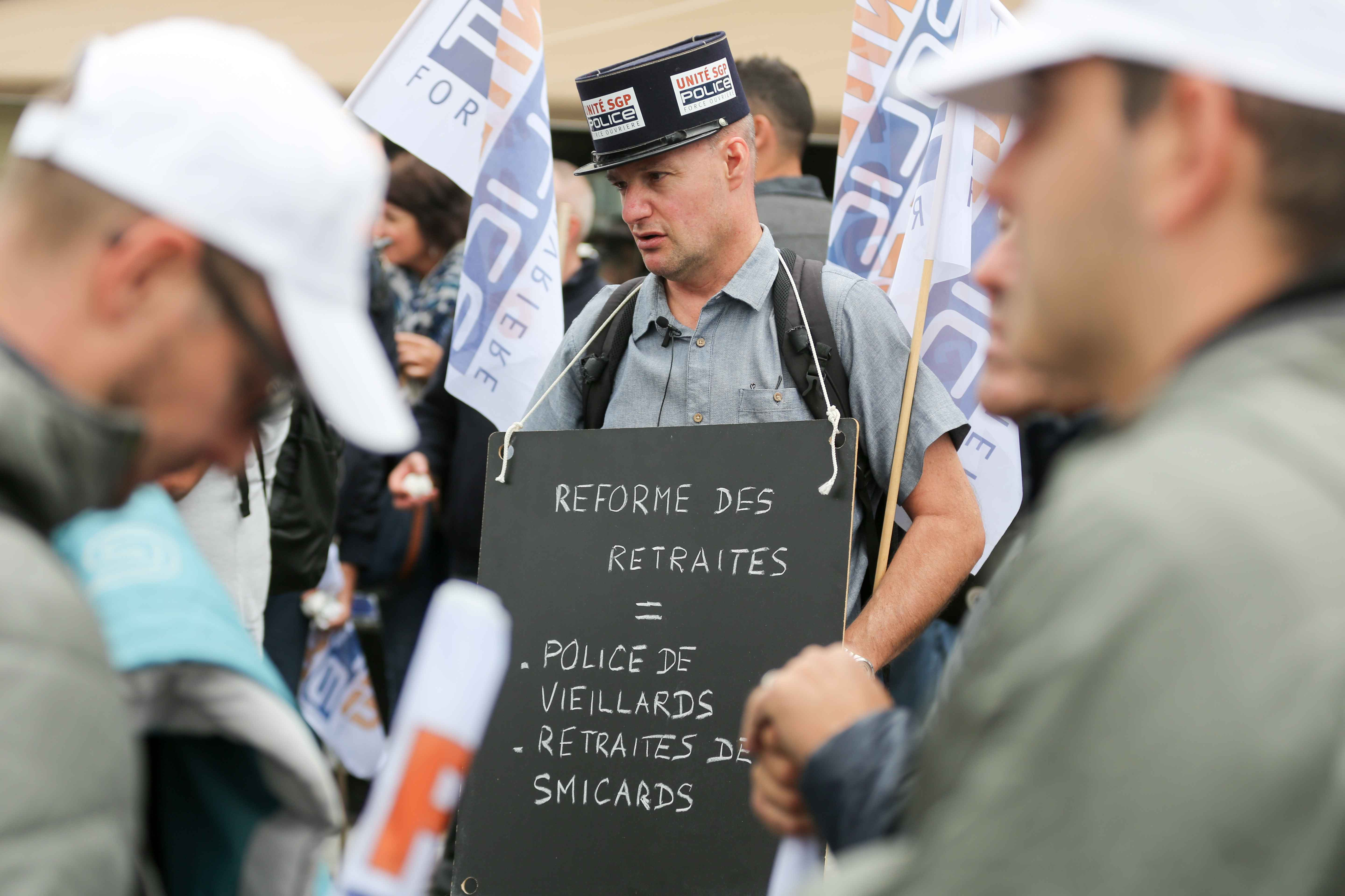 A demonstrator hold a sign reading « Pension reform = old people's police, minimum pension » during the ''Walk of Wrath'' of the Policemen in Paris (France) on October 2, 2019. At the call of the National Police unions, several thousand police officers