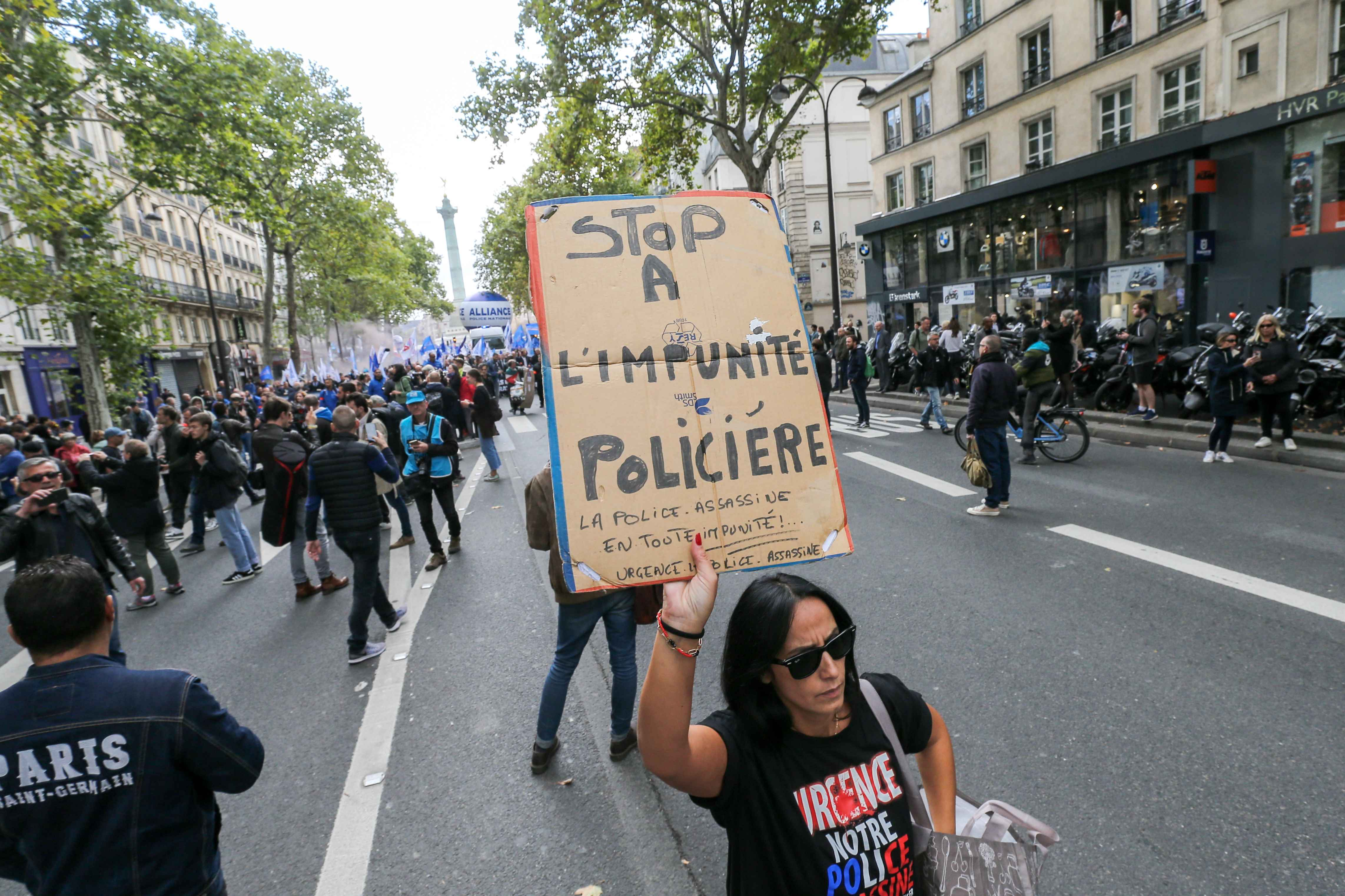 A woman holds a sign reading « stop to police impunity » during the ''Walk of Wrath'' of the Policemen in Paris (France) on October 2, 2019. At the call of the National Police unions, several thousand police officers demonstrated in Place de la Bastille