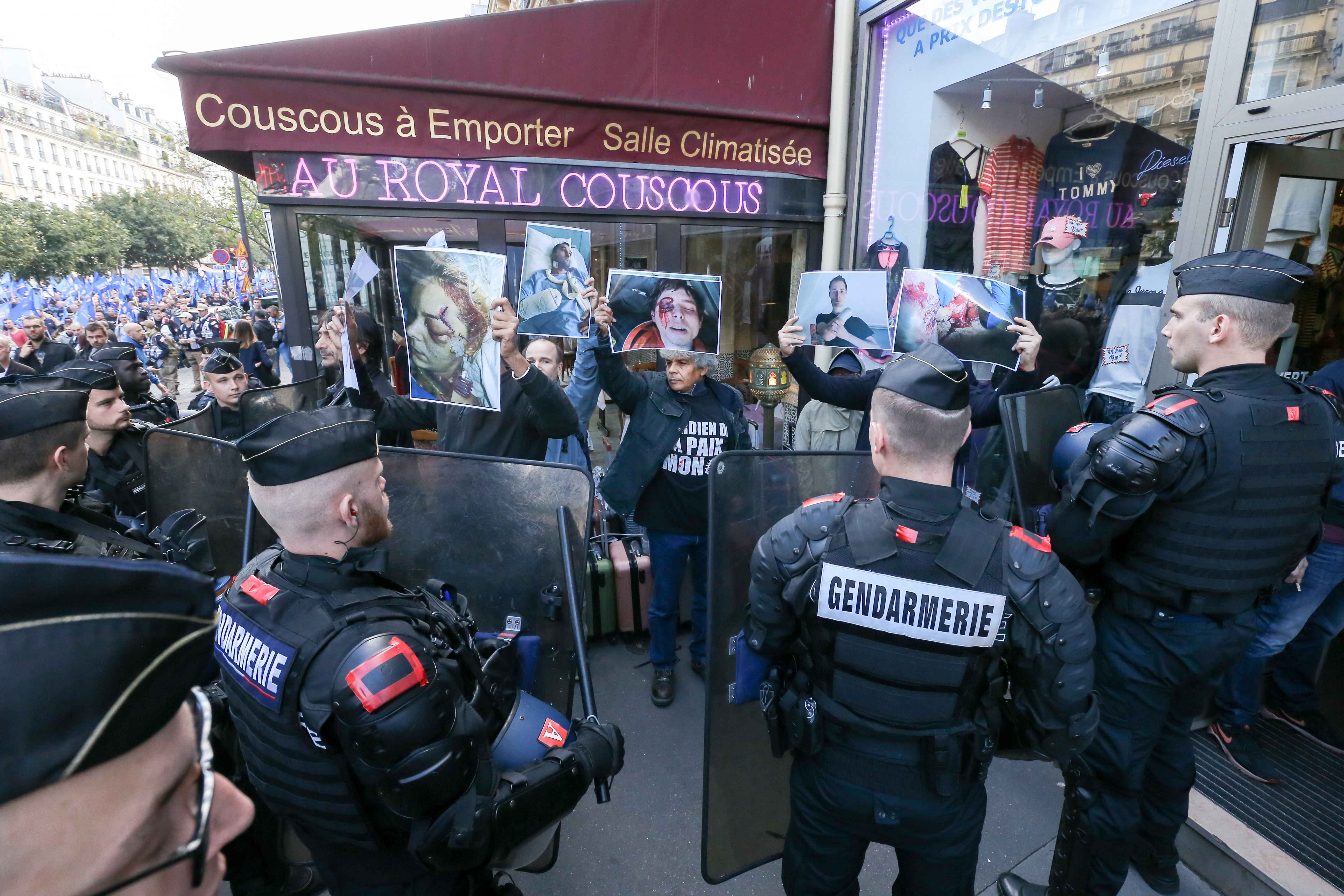 Counter-demonstrators hold signs with the photo of personns injured during the yellow vest demonstrations during the ''Walk of Wrath'' of the Policemen in Paris (France) on October 2, 2019. At the call of the National Police unions, several thousand police
