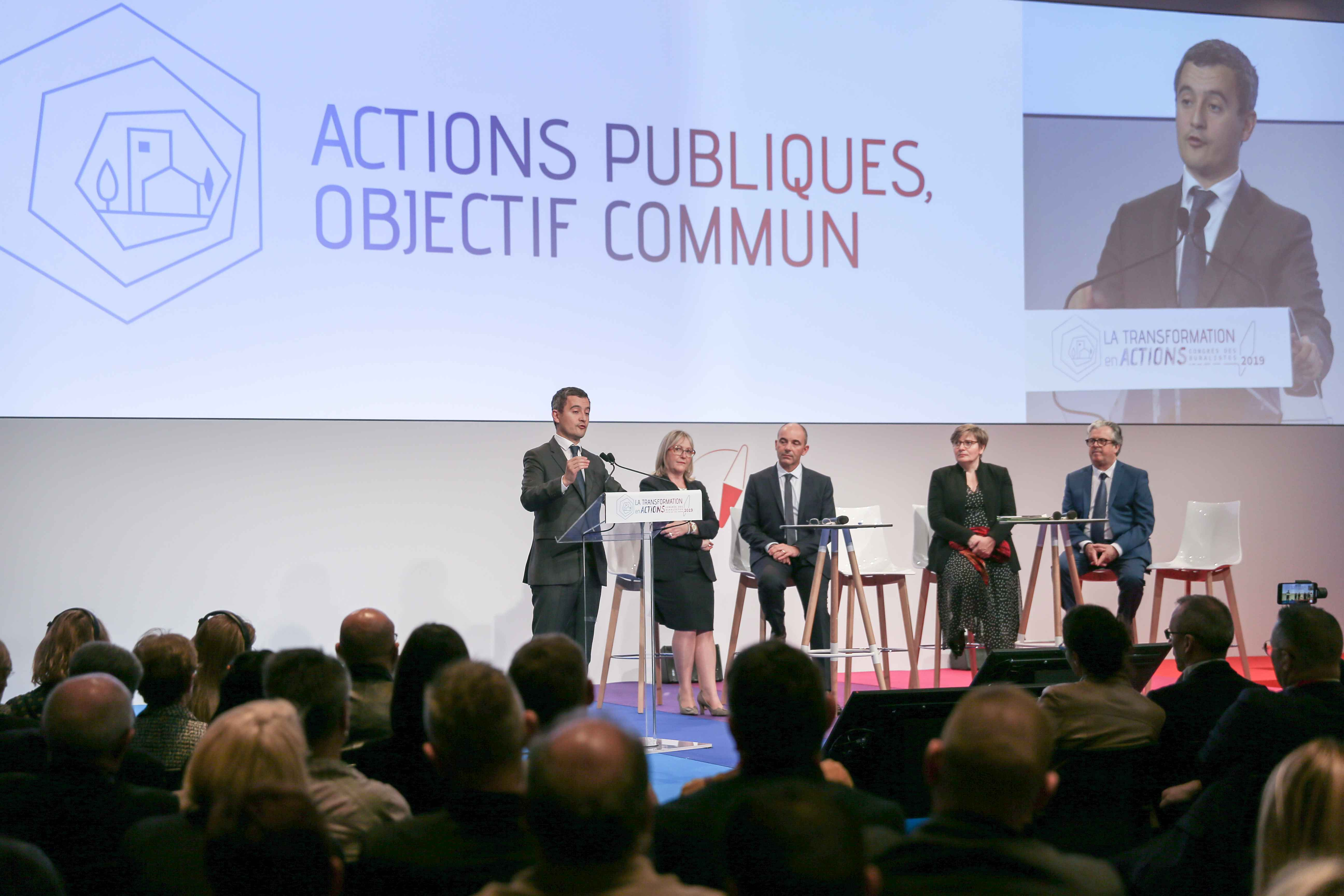 French Minister for Public Action and Accounts Gerald Darmanin (L) adresses tobacconists, in front of by Philippe Coy (3R), President of the National Tobacconists  Confederation, during the Congress of the Confederation in Paris, on October 10, 2019. In th
