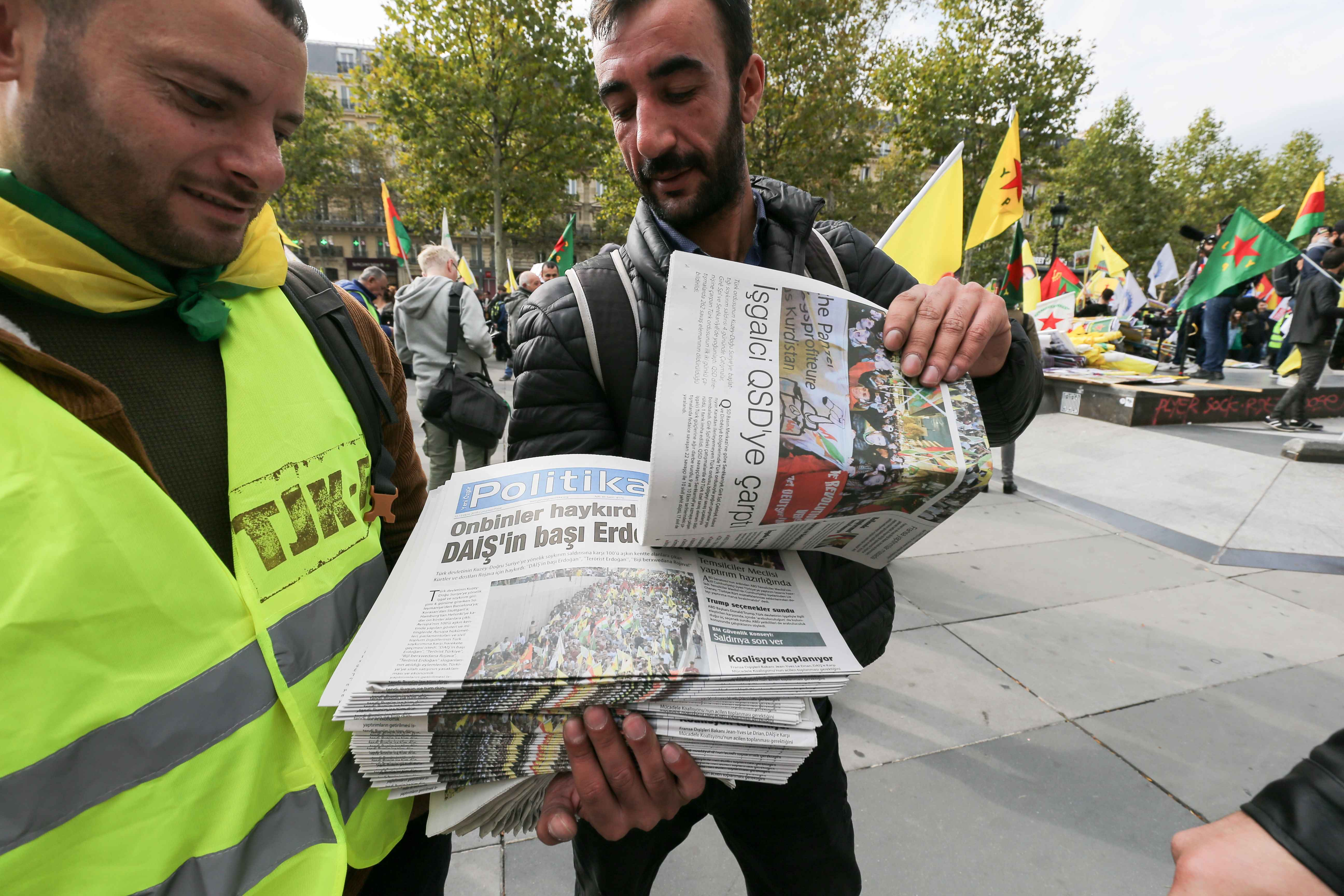 A man is selling newspapers about the Kurds in Syria during a demonstration at the place de la Republique in Paris, on October 12, 2019, in support of the Kurds and against the Turkish offensive in Syria. On October 9, 2019, the Turkish military began its
