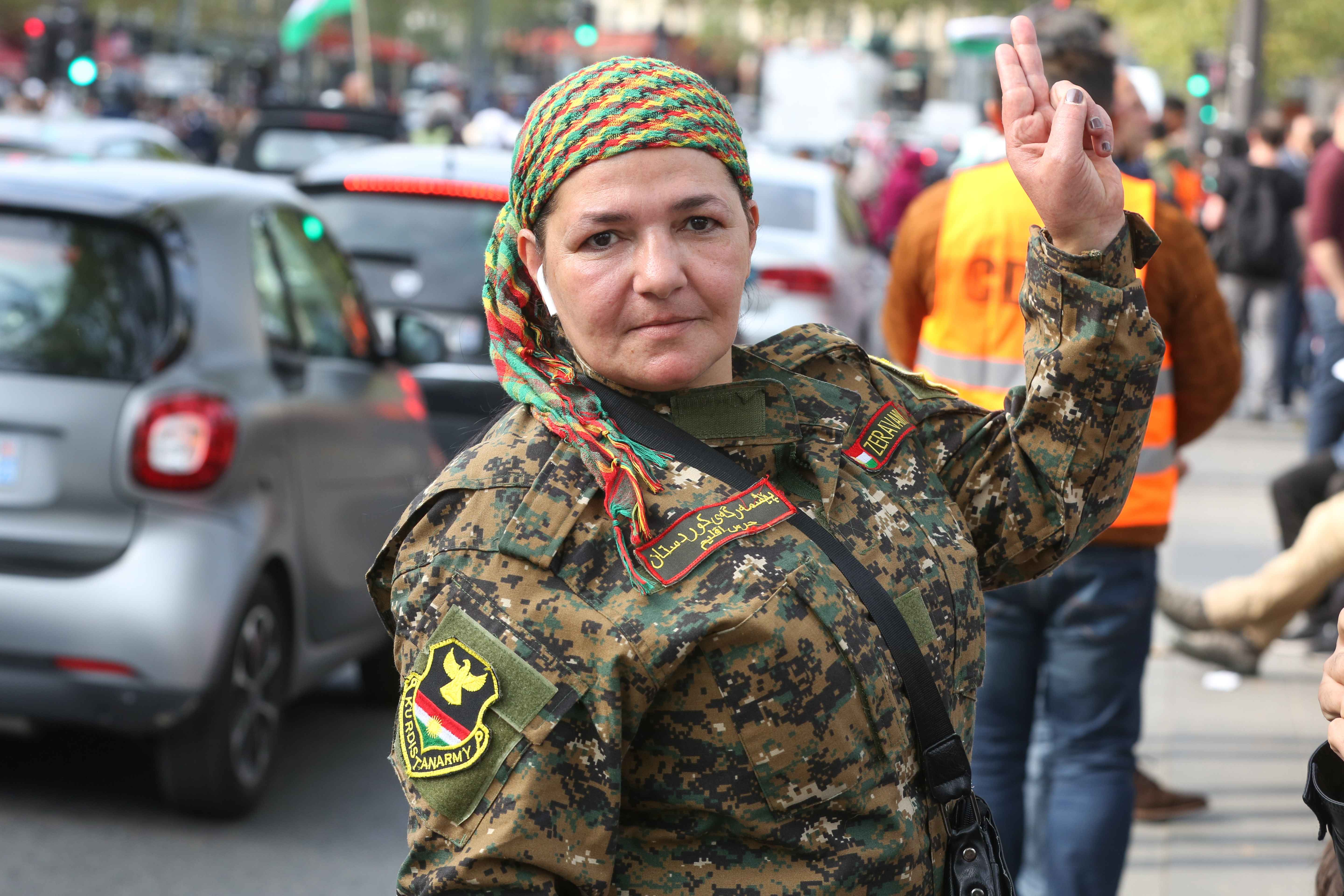 A woman is wearing a battle dress with the Kurdistan Army insignia during a demonstration at the place de la Republique in Paris, on October 12, 2019, in support of the Kurds and against the Turkish offensive in Syria. On October 9, 2019, the Turkish milit