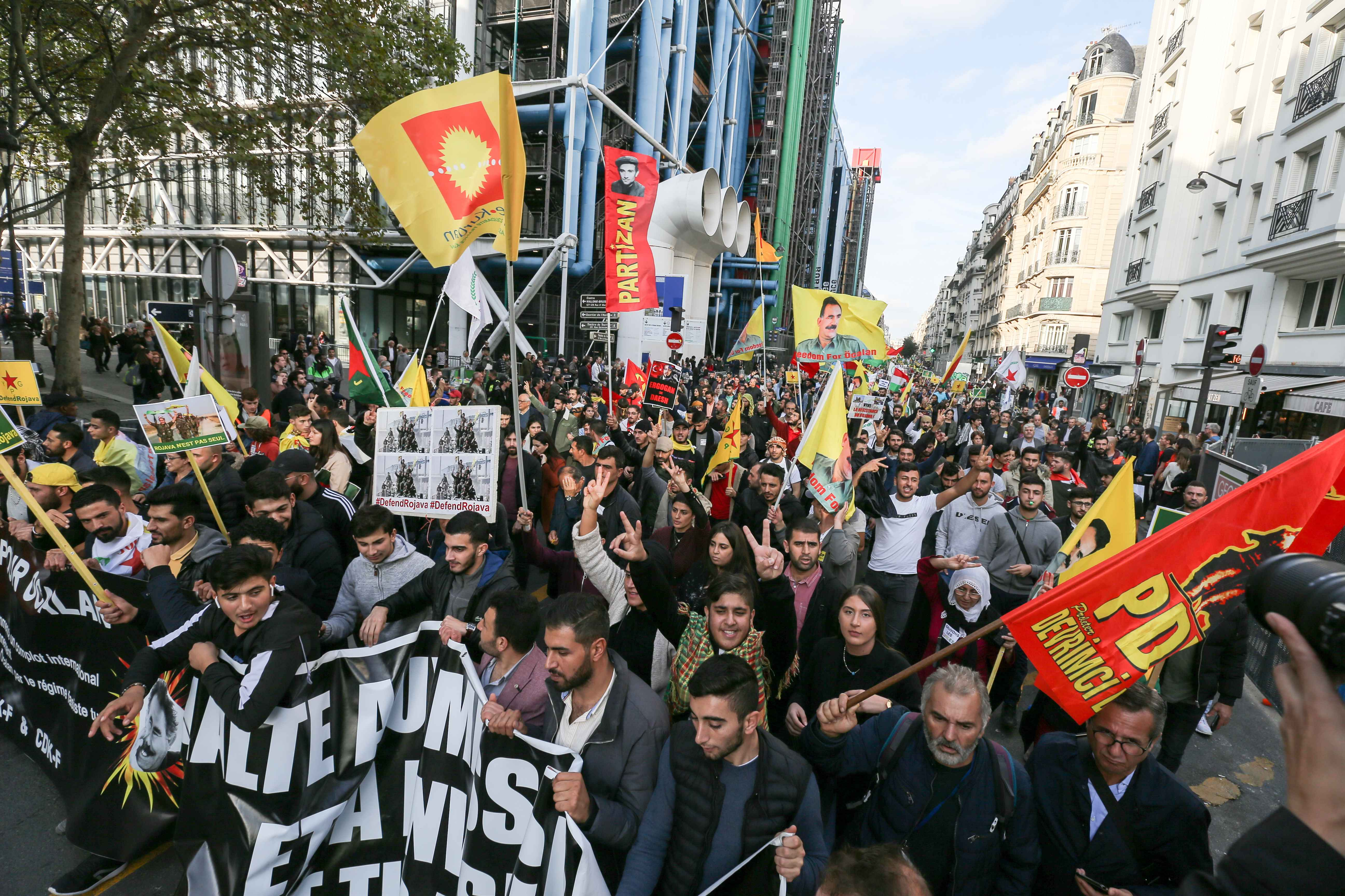 People walk in front of the Pompidou Center in Paris, on October 12, 2019, in support of the Kurds and against the Turkish offensive in Syria. On October 9, 2019, the Turkish military began its assault against Kurdish-held territory in northern Syria , pum