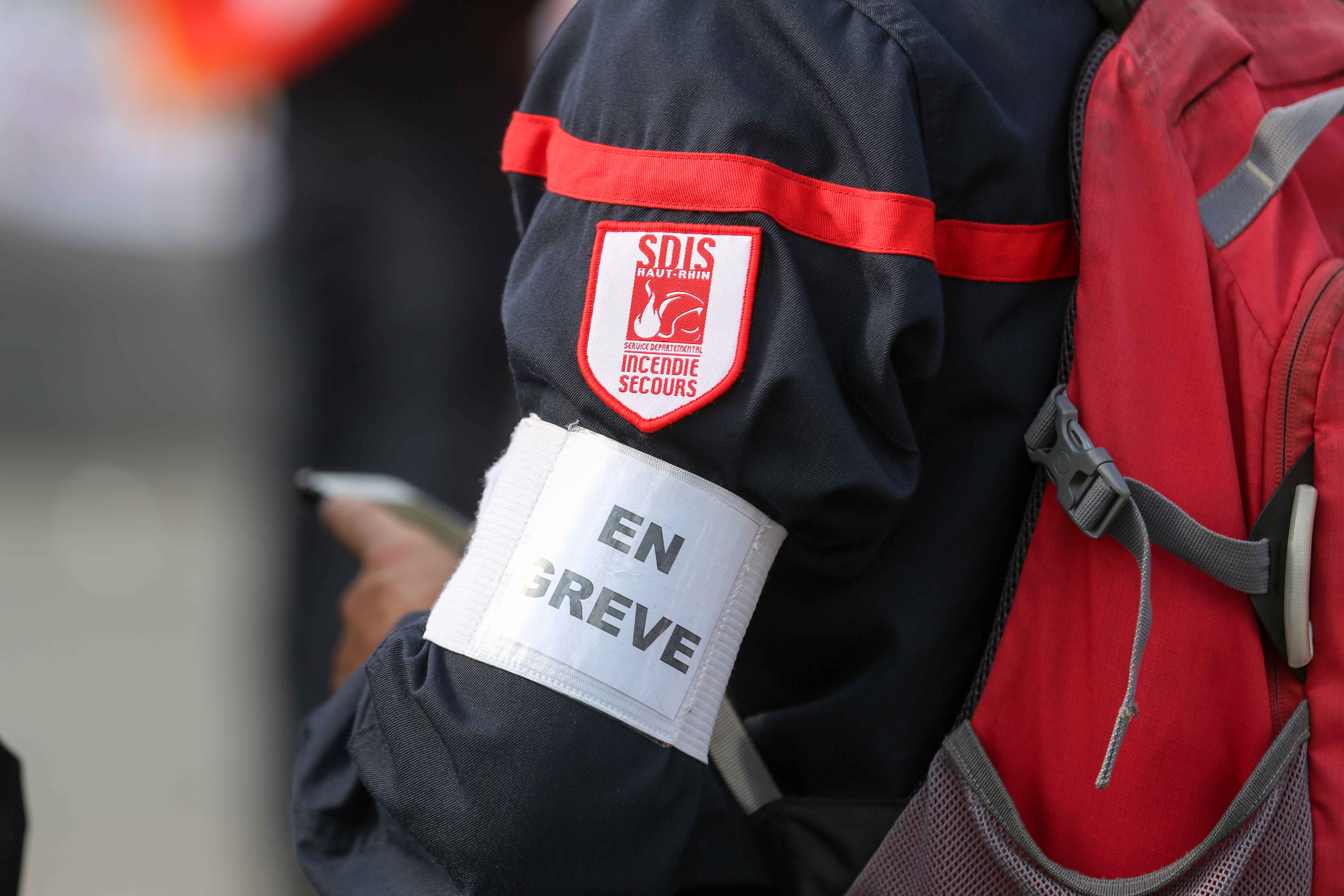 Firefighter wears an armband reading « On strike » during the day of mobilization and national demonstration of the professional French firefighters in Paris, on October 15, 2019.