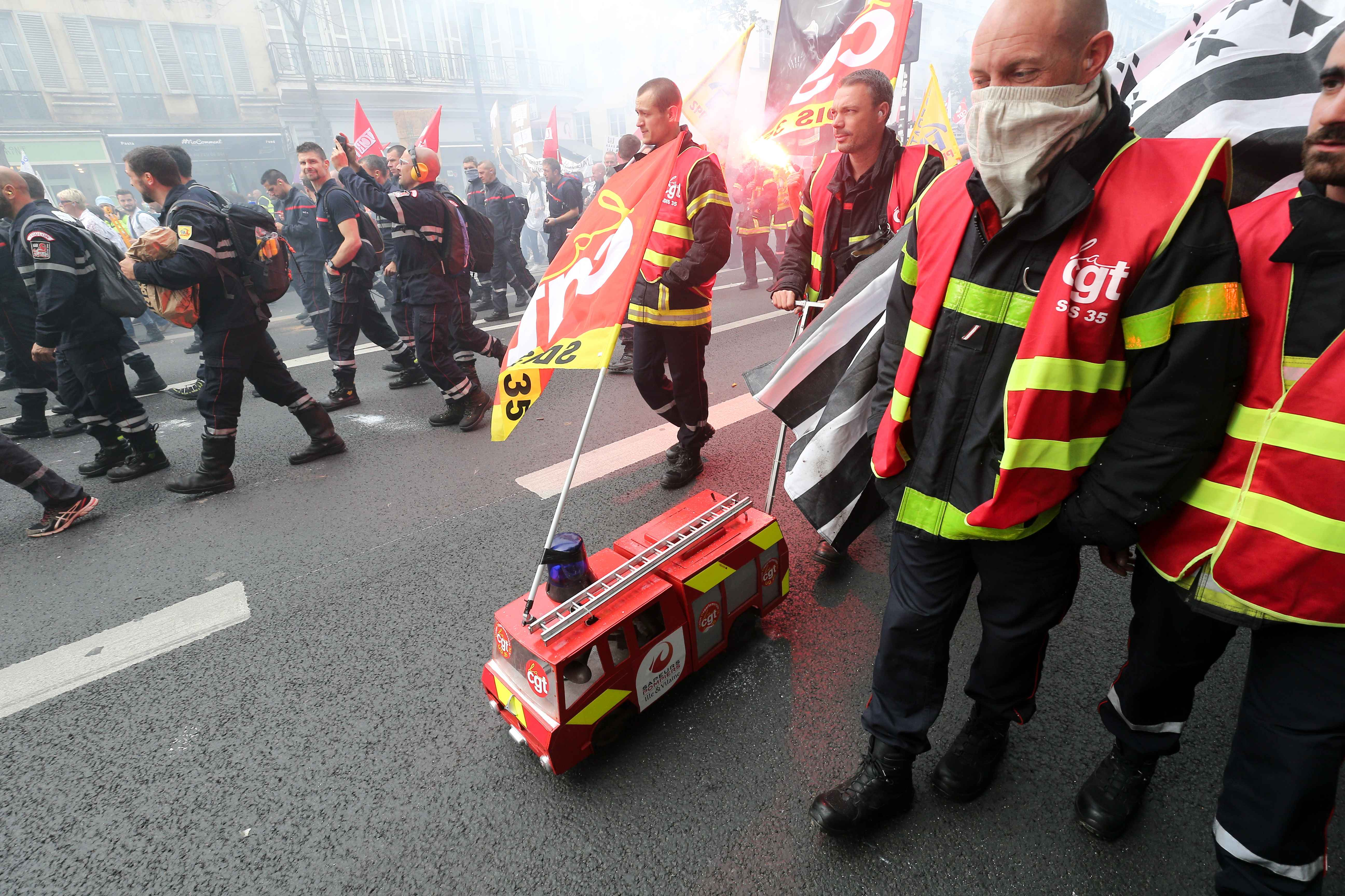 A firefighter push a firefighter vehicle toy during the day of mobilization and national demonstration of the professional French firefighters in Paris, on October 15, 2019.