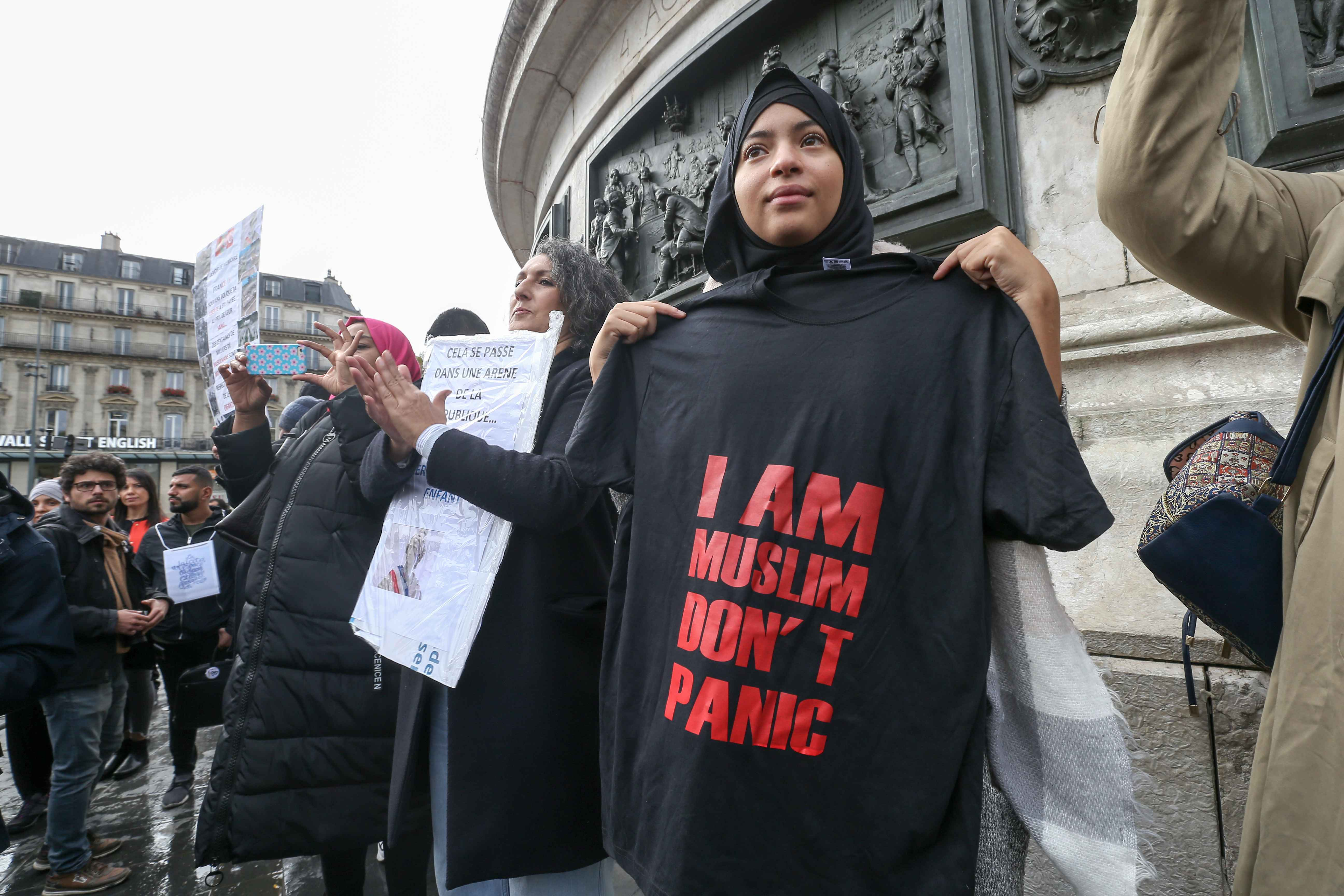 "Woman holds a shirt reading ""I am Muslim, don't panic » during a demonstration on October 19, 2019 on the place de la Republique in Paris. A new row over secularism and the wearing of the Islamic hijab in public buildings has erupted in France after a f"