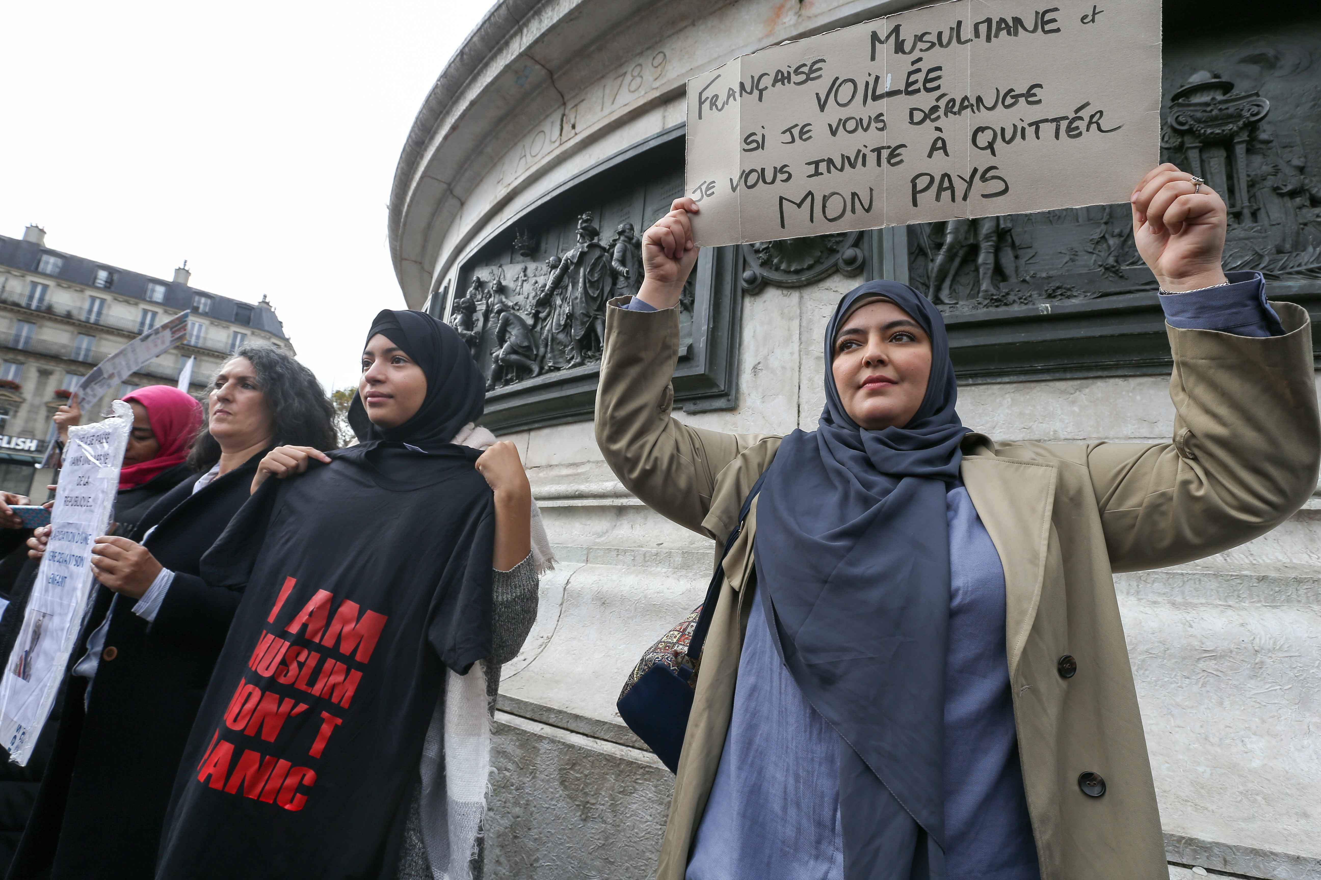 "Woman holds a placard reading ""French Muslm and veiled : if I'm bothering you, I invite you to leave this country » during a demonstration on October 19, 2019 on the place de la Republique in Paris. A new row over secularism and the wearing of the Islam"