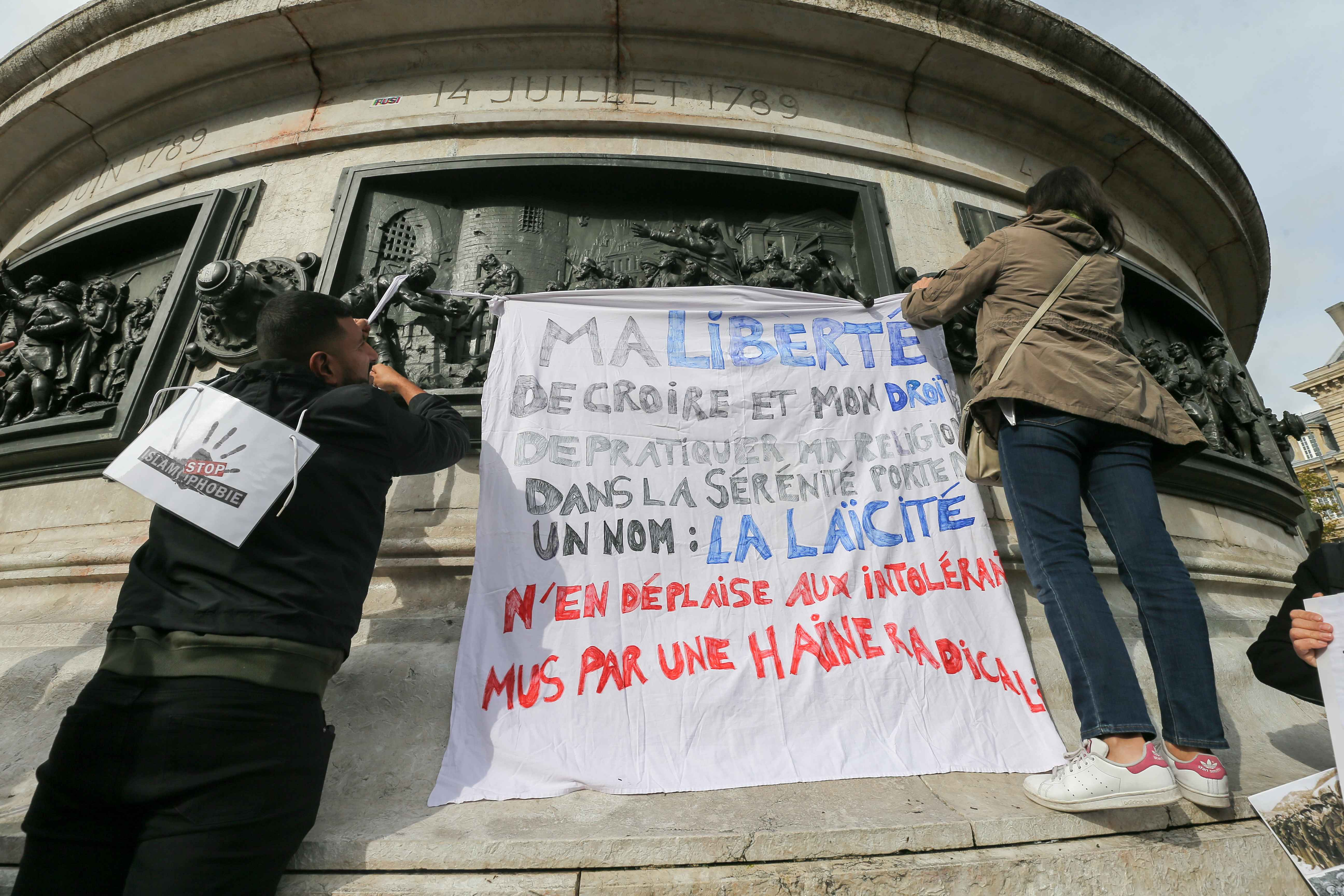 Protestors hang a placard reading « My freedom to believe in a religion and my rights to practice my religion in the serenity have a name : secularism » during a demonstration on October 19, 2019 on the place de la Republique in Paris. A new row over sec