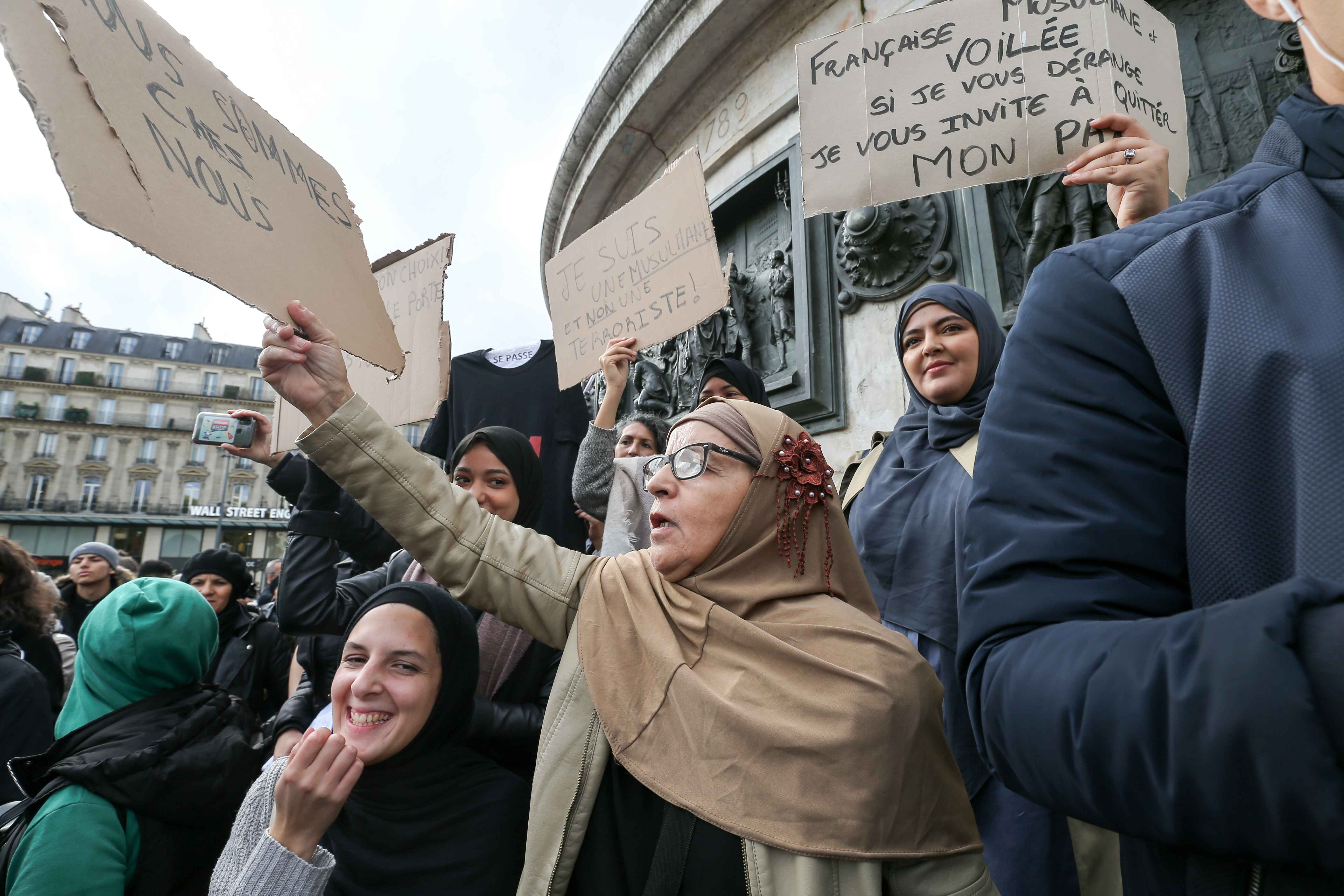 Woman holds a placard reading « We are home » during a demonstration on October 19, 2019 on the place de la Republique in Paris. A new row over secularism and the wearing of the Islamic hijab in public buildings has erupted in France after a far-right po