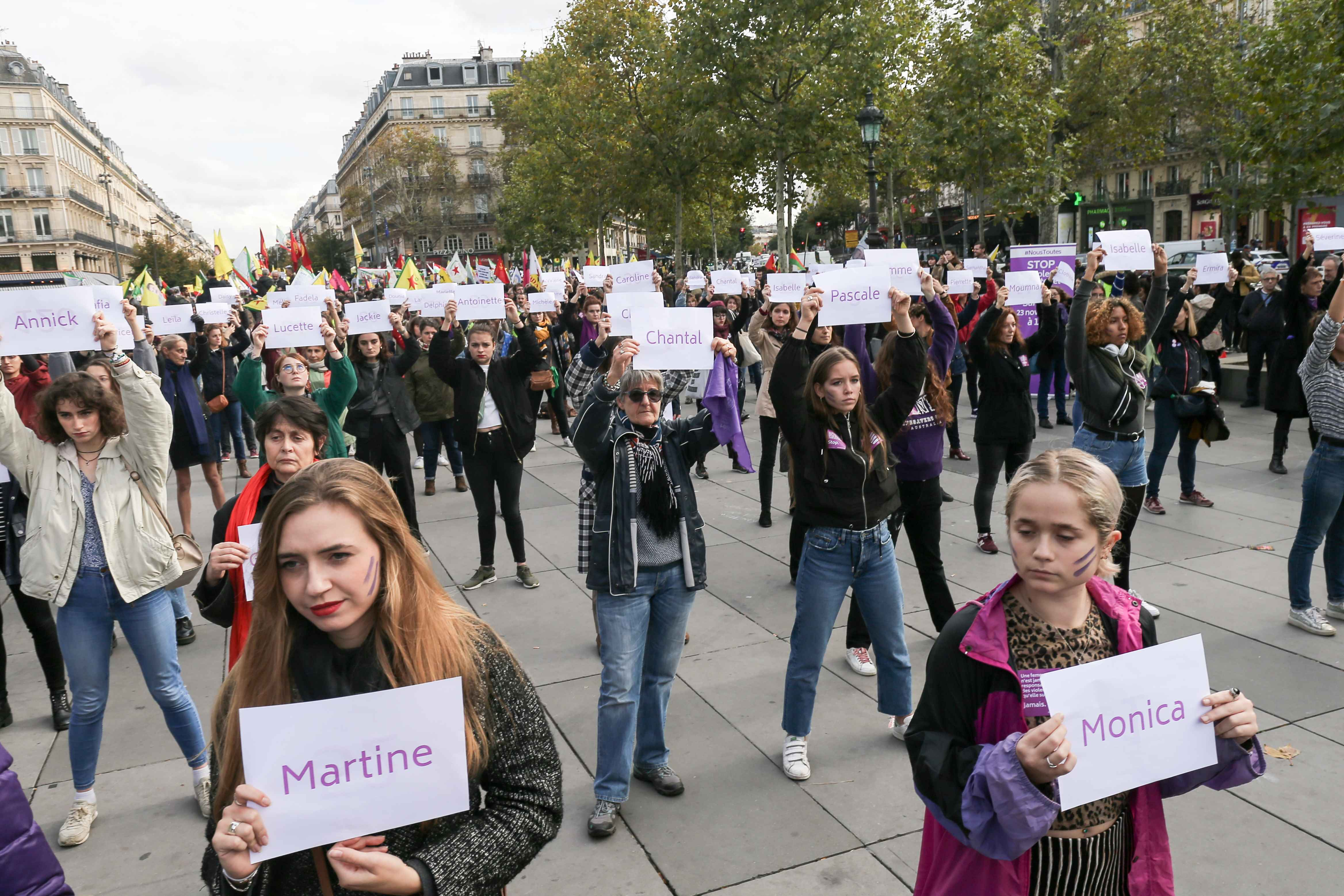 "Women hold placards reading names of women victims of femicide place de la Republique, in Paris, during a ""die-in"" demonstration called by different associations to denounce feminicides in France, on October 19, 2019. 121st victim of a femicide in France i"