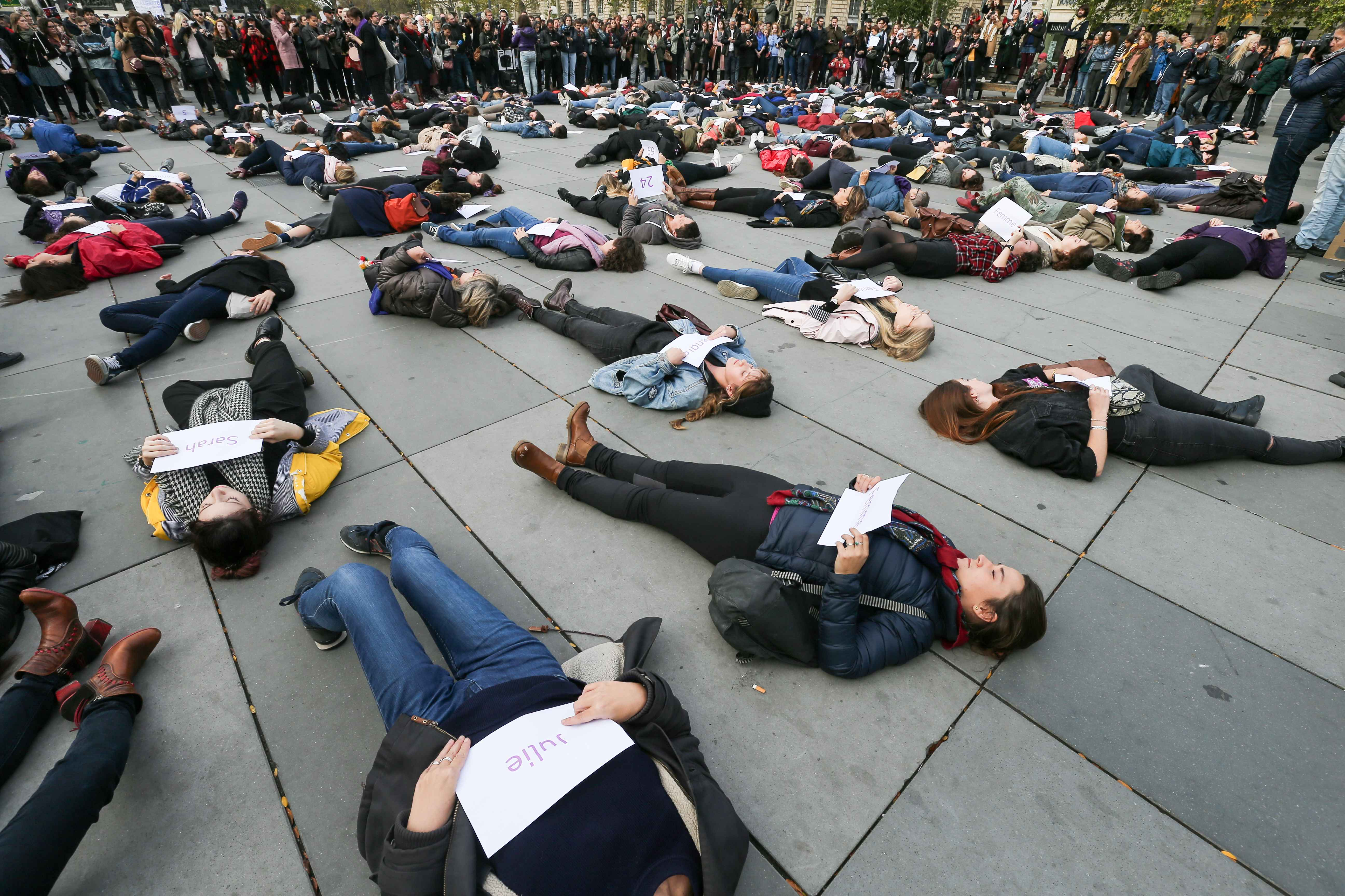 "Women hold placards reading names of women victims of femicide as they lay on the ground of place de la Republique, in Paris, during a ""die-in"" demonstration called by different associations to denounce feminicides in France, on October 19, 2019. 121st vic"