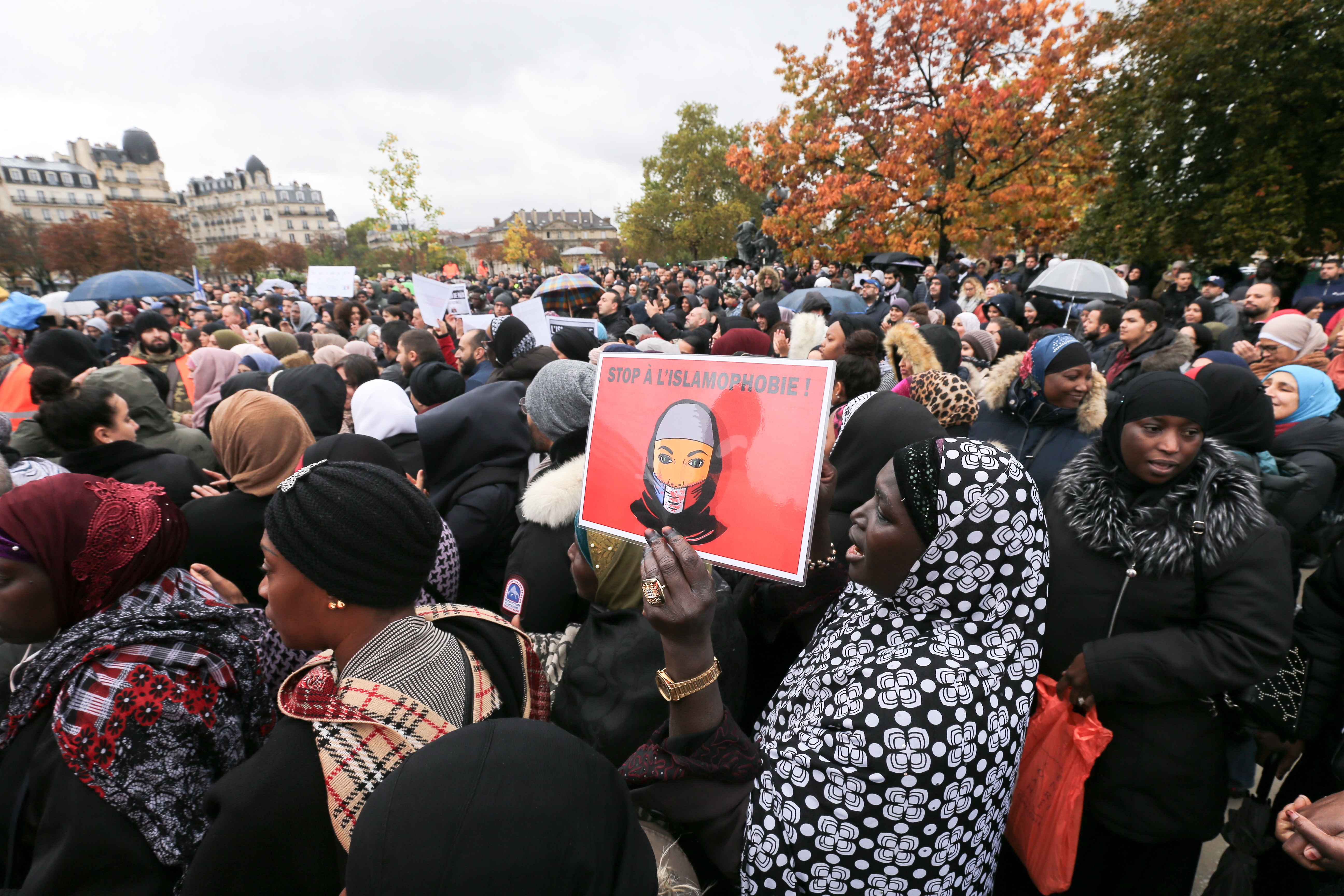 A woman holds a placard reading « Stop to islamophobia » as she takes part in a gathering place de la Nation, one of the Paris' major crossroad on October 27, 2019, to protest against Islamophobia and media bias in France. A new row over secularism and