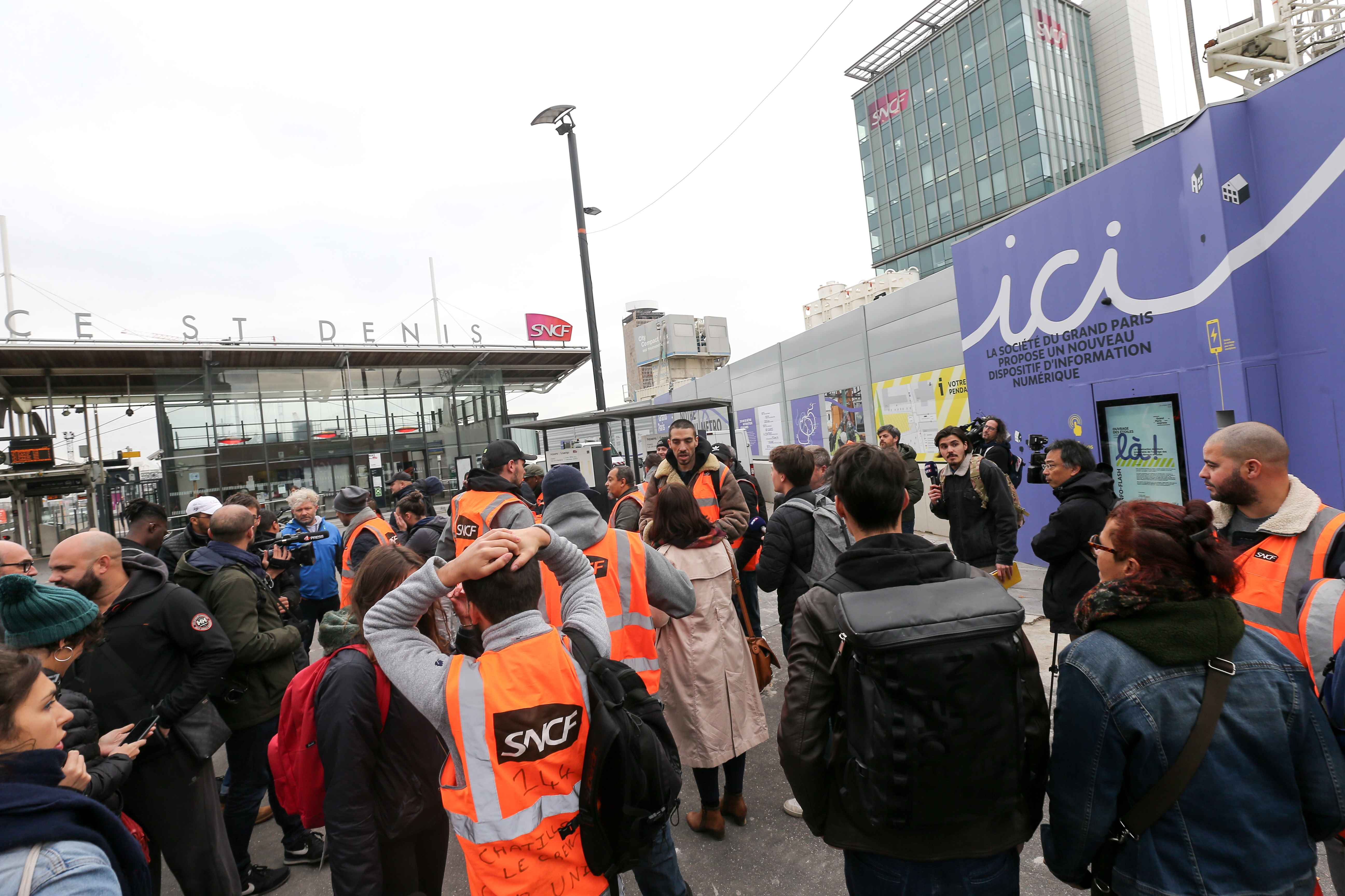 Railway workers wearing jackets of France's national state-owned railway company (SNCF) and workers of Chatillon TGV Technicentre, protest in front of the headquarters of the SNCF company, in Saint-Denis, near Paris, on October 29, 2019. Originally a local
