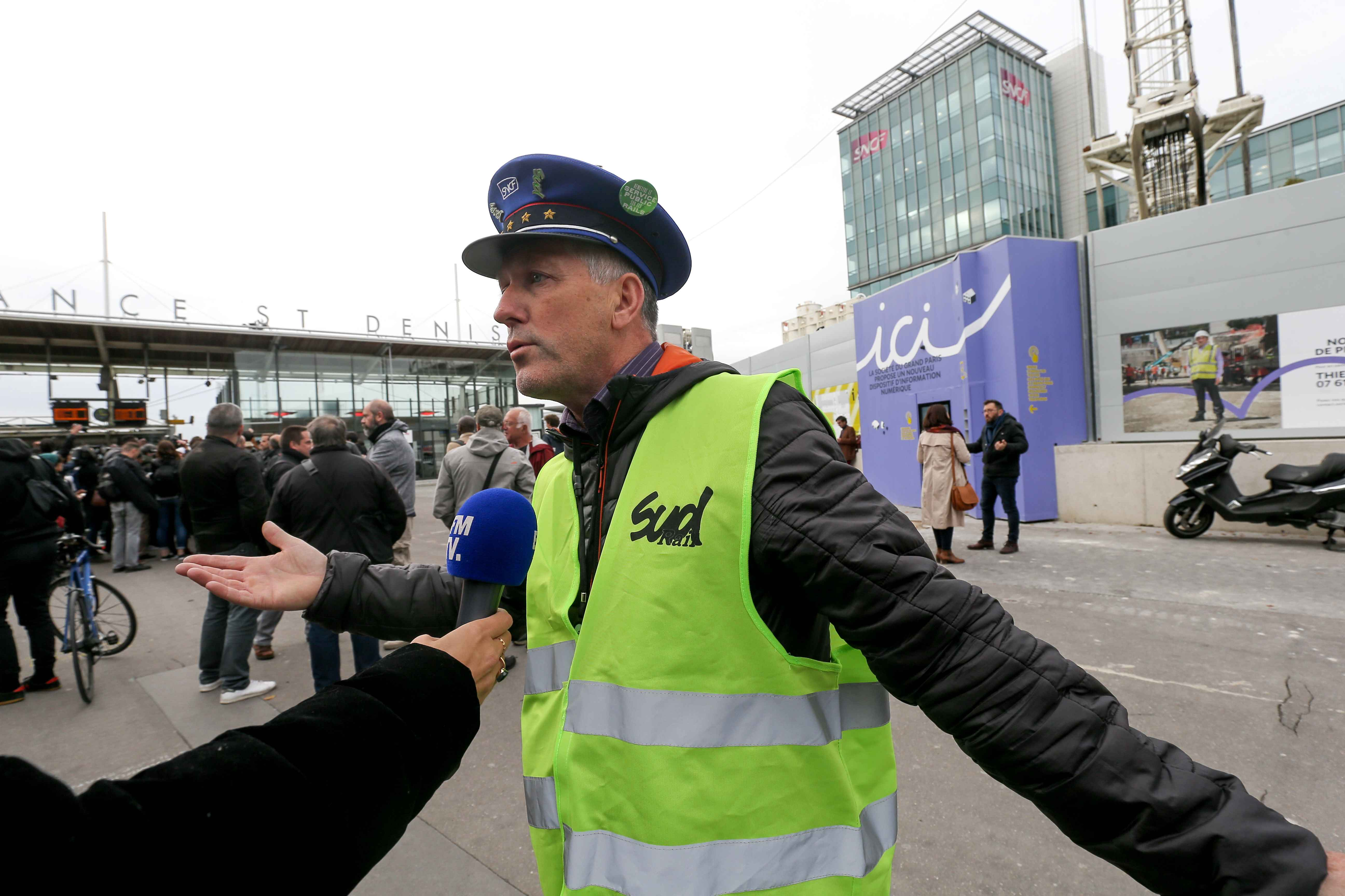 Railway worker wearing jacket of France's national state-owned railway company (SNCF) from the Chatillon TGV Technicentre speaks with press as he protests in front of the headquarters of the SNCF company, in Saint-Denis, near Paris, on October 29, 2019. Or