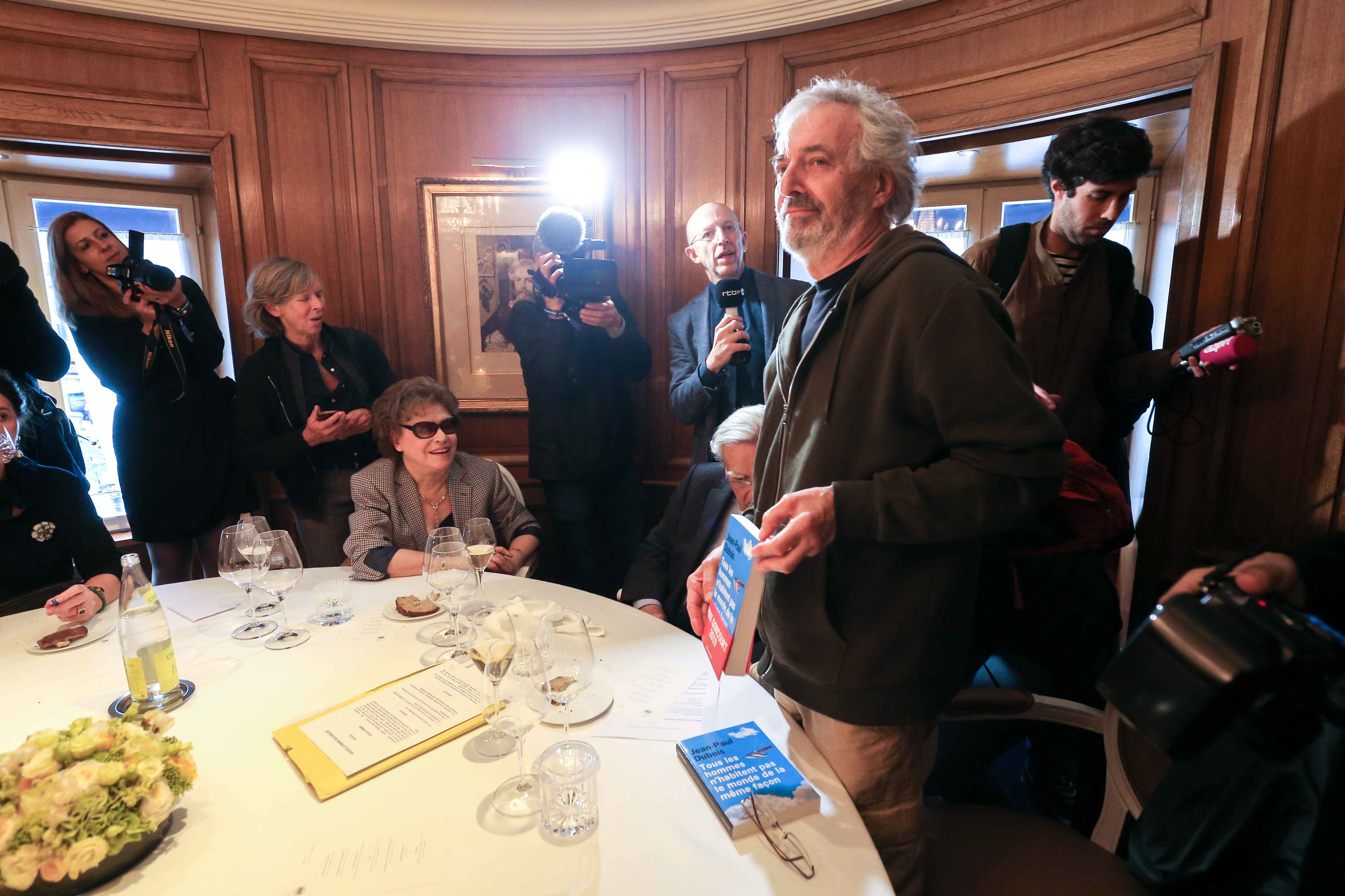 "French author Jean-Paul Dubois poses with his novel ""Tous les hommes n'habitent pas le monde de la même facon - All men do not live in the world in the same way ""(L'Olivier) in the Drouant restaurant in Paris after winning the France's literary prize, the"