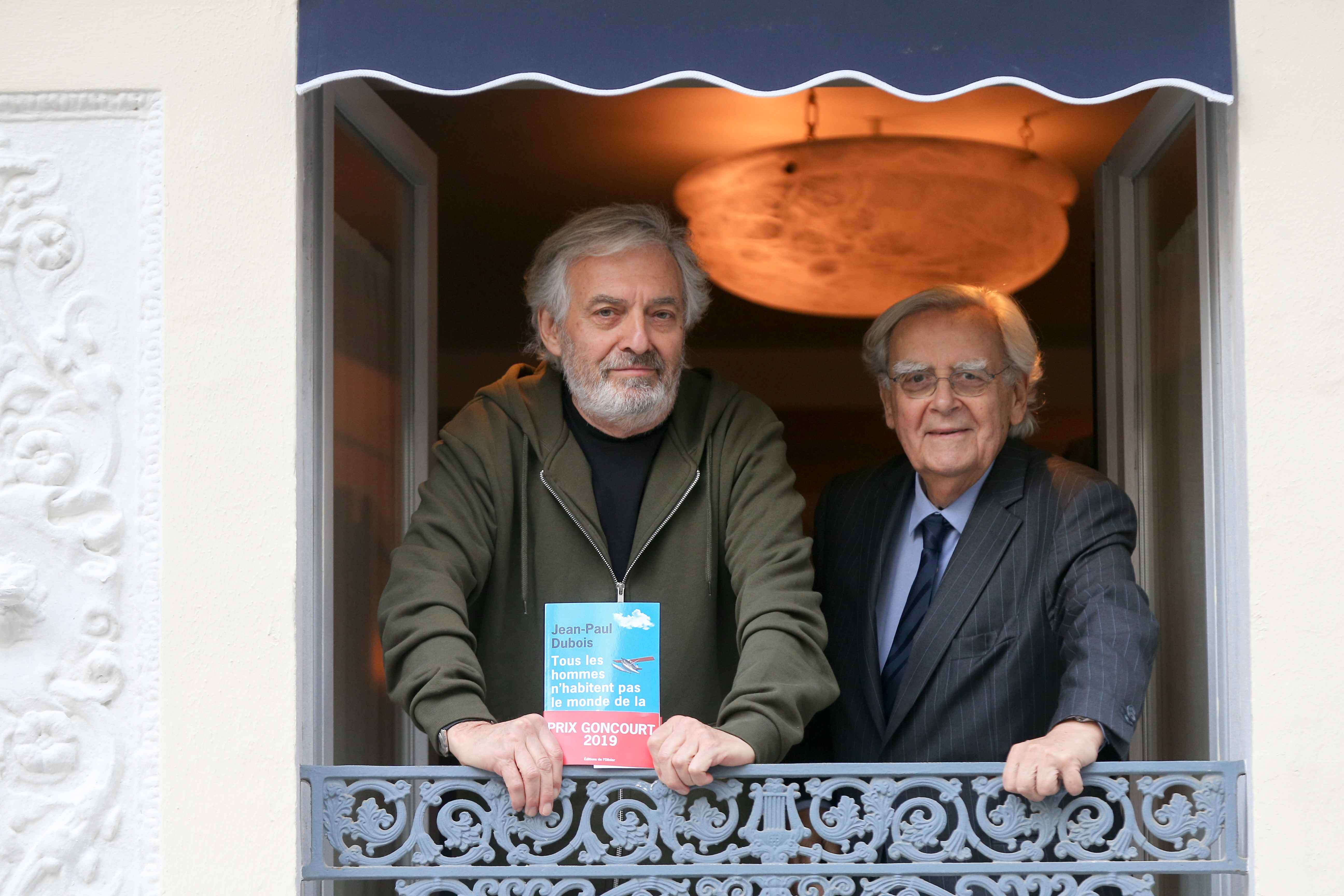 "French author Jean-Paul Dubois (L) acompanied with French jourmalist and member of the jury of the Prix Goncourt Bernard Pivot (R) poses with his novel ""Tous les hommes n'habitent pas le monde de la même facon - All men do not live in the world in the sam"