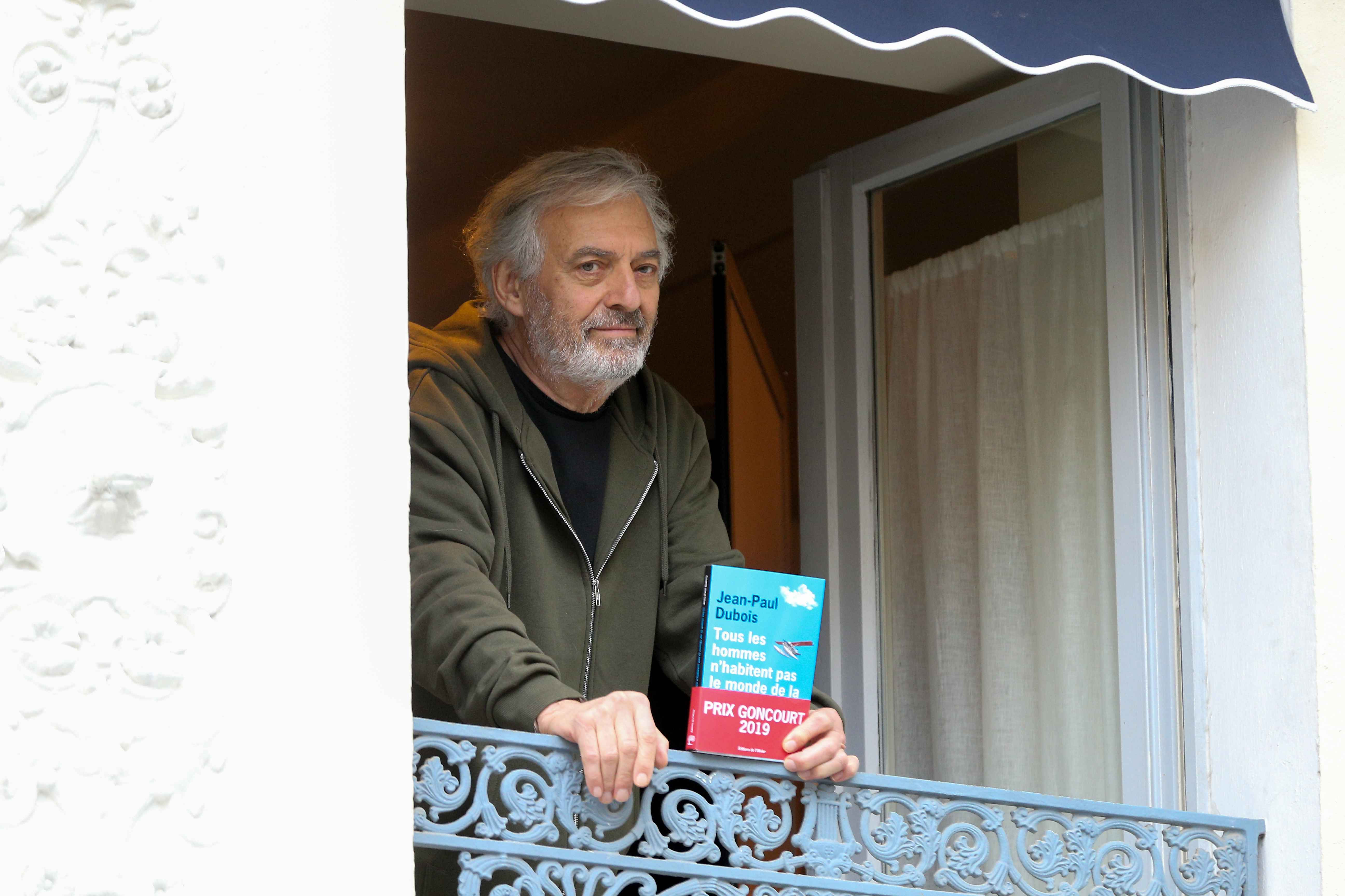 "French author Jean-Paul Dubois poses with his novel ""Tous les hommes n'habitent pas le monde de la même facon - All men do not live in the world in the same way ""(L'Olivier) at the window of the Drouant restaurant in Paris after winning the France's liter"