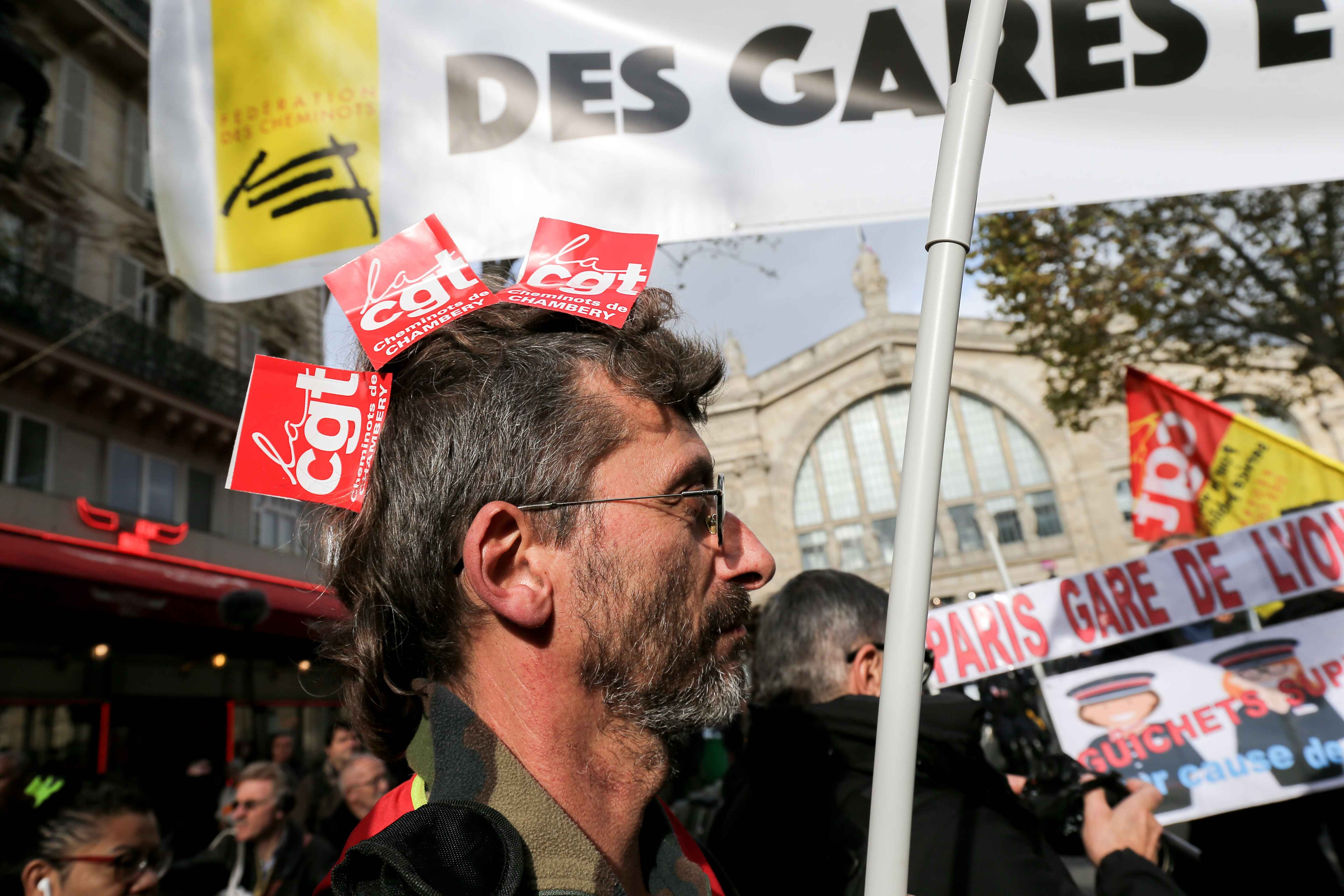 A CGT union railway worker takes part in a demonstration of employees of the state-owned rail operator SNCF called by CG union on November 5, 2019 in front of the Gare du Nord in Paris to defend SNCF's internal public service, denounce their living and wor
