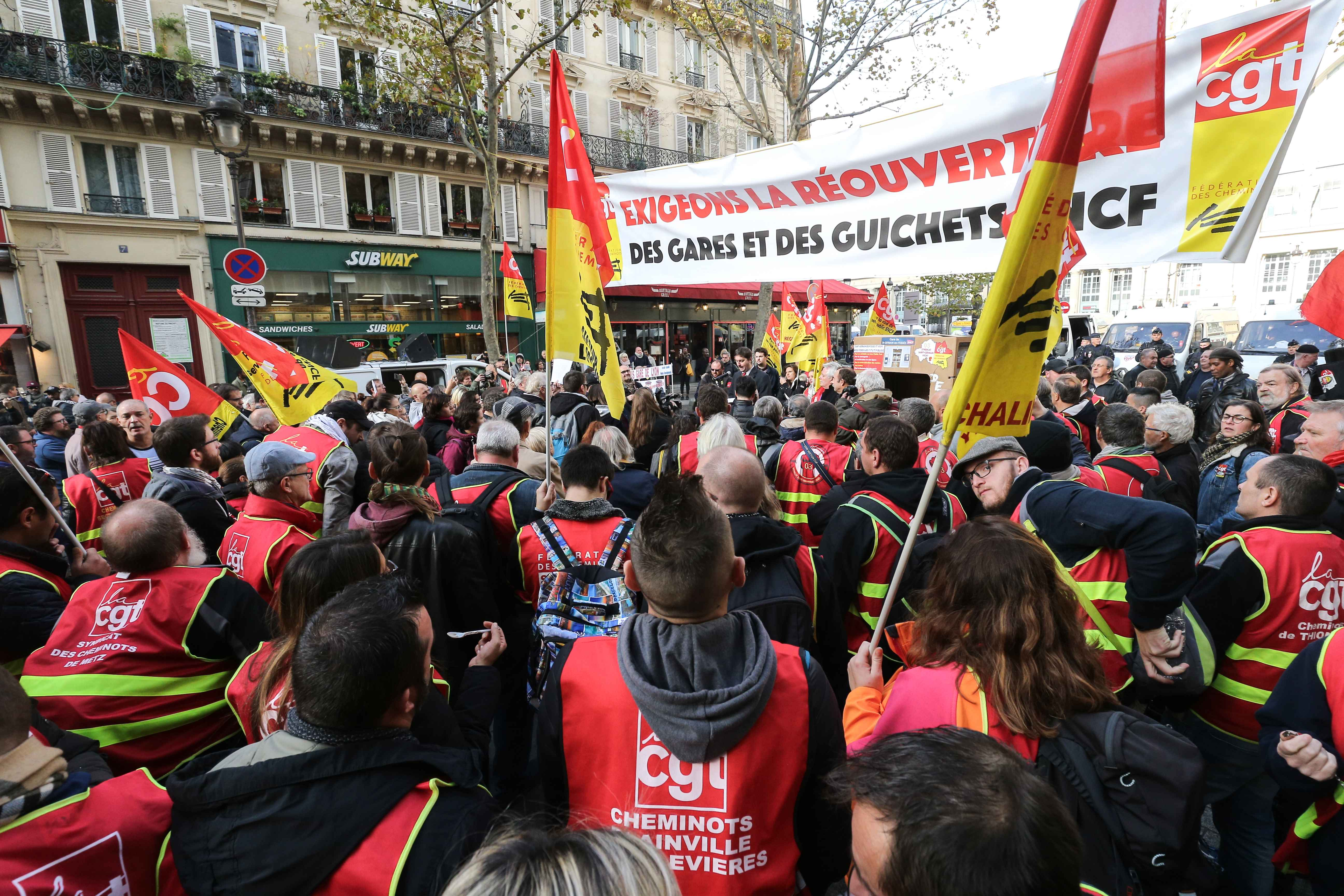 "The CGT union railway workers gather in front of a banner ""Let's demand the reopening of SNCF stations and ticket offices"" as they take part in a demonstration of employees of the state-owned rail operator SNCF called by CG union on November 5, 2019 in fro"