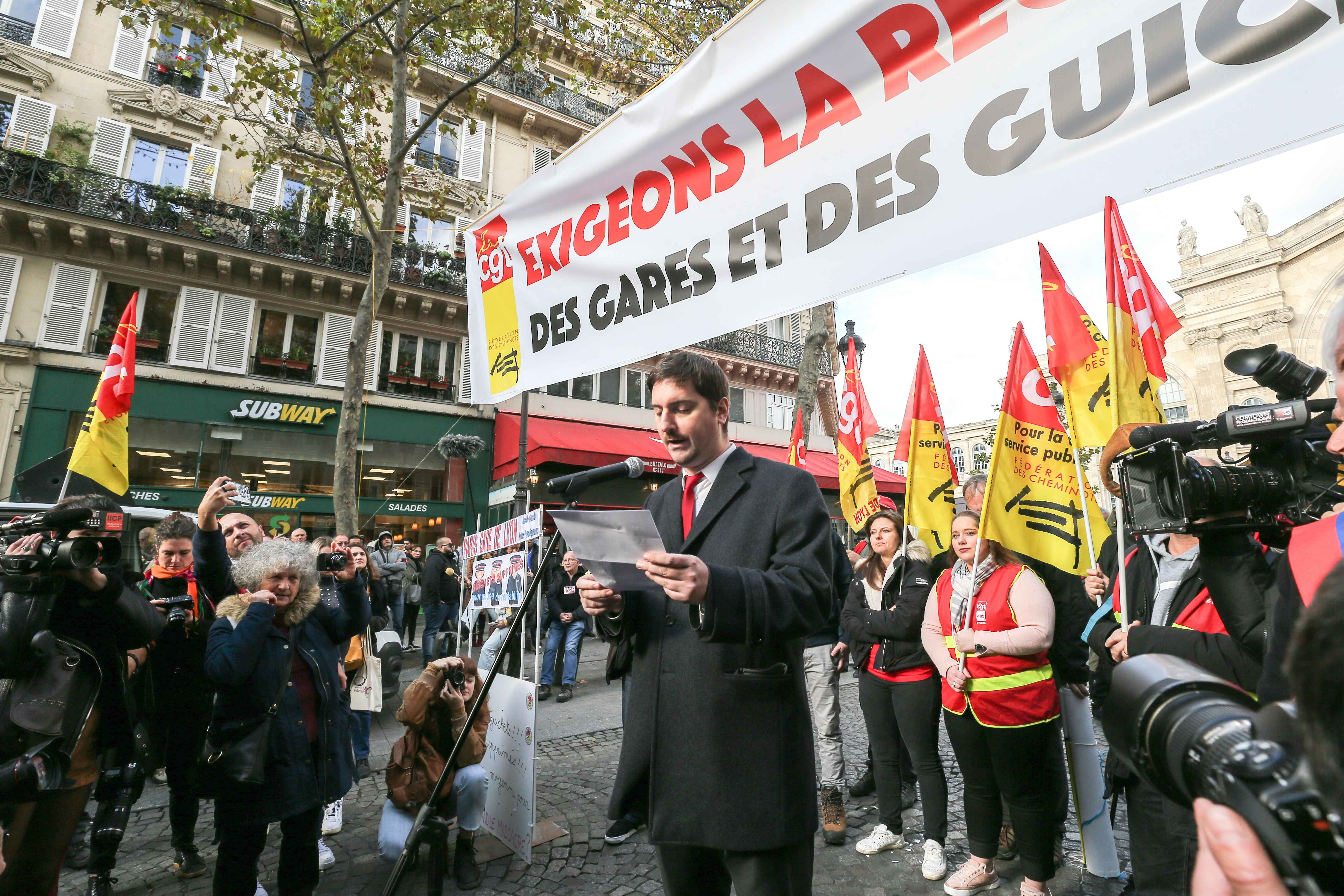 "CGT Cheminots union representative Laurent Brun speaks in front of a banner reading ""Let's demand the reopening of SNCF stations and ticket offices""  during a gathering of employees of the state-owned rail operator SNCF called by CG union on November 5, 20"