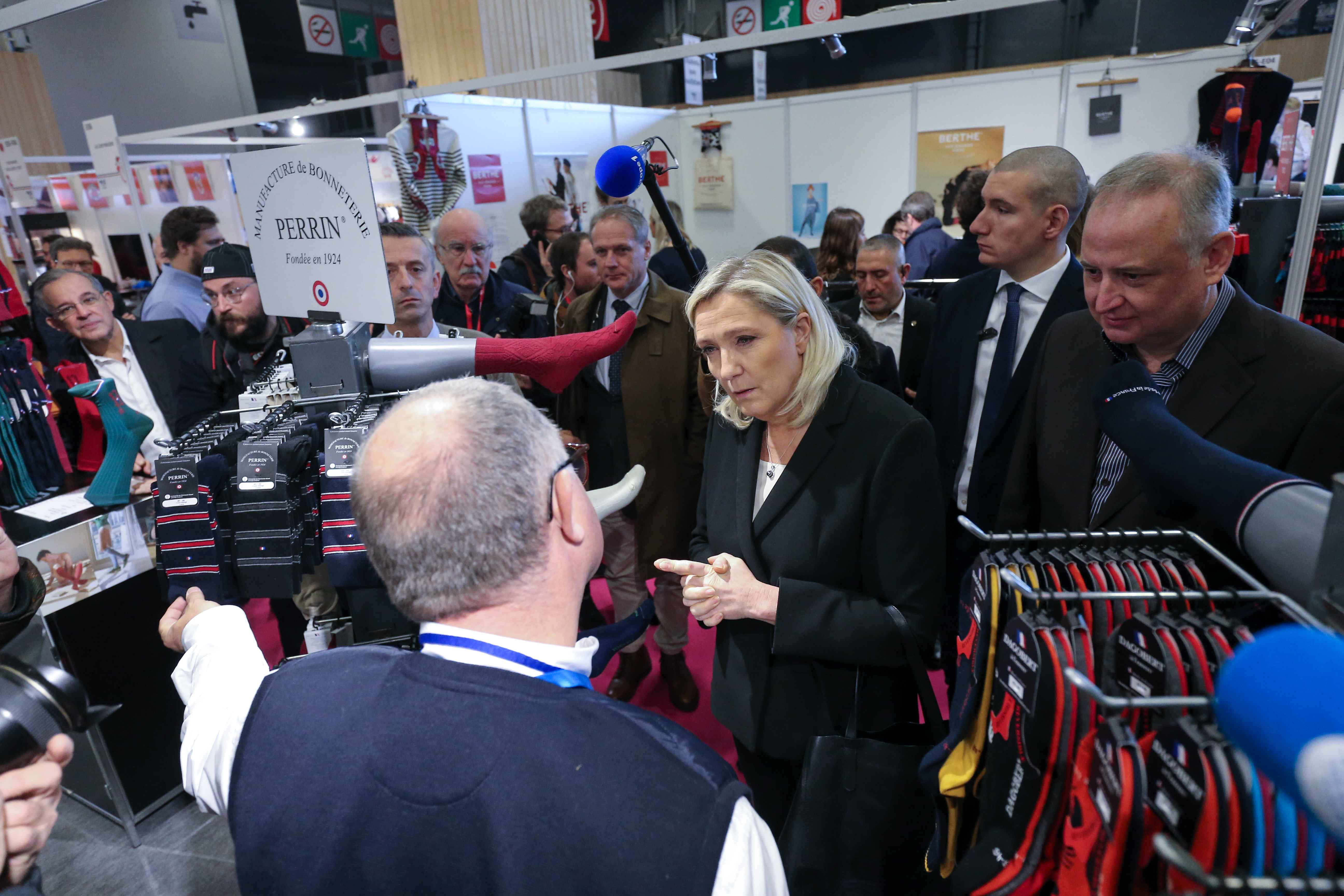 French far-right Rassemblement National (RN) party's president and MP Marine Le Pen (C) speaks with the owner of a stall as she visits the Made in France Fair, on November 9, 2019, at the Porte de Versailles, in Paris.