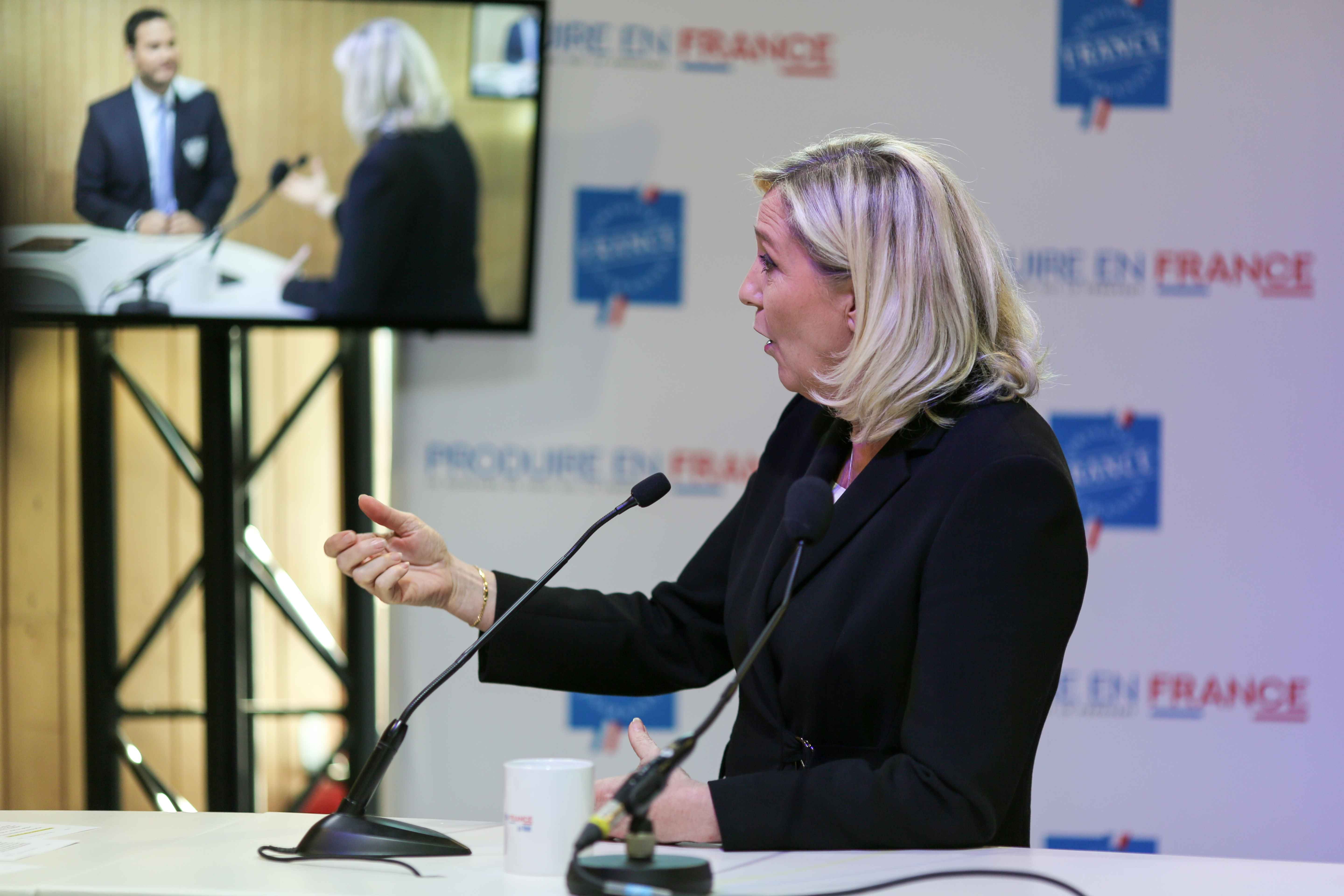 French far-right Rassemblement National (RN) party's president and MP Marine Le Pen (C) talks with the press as she visits the Made in France Fair, on November 9, 2019, at the Porte de Versailles, in Paris.