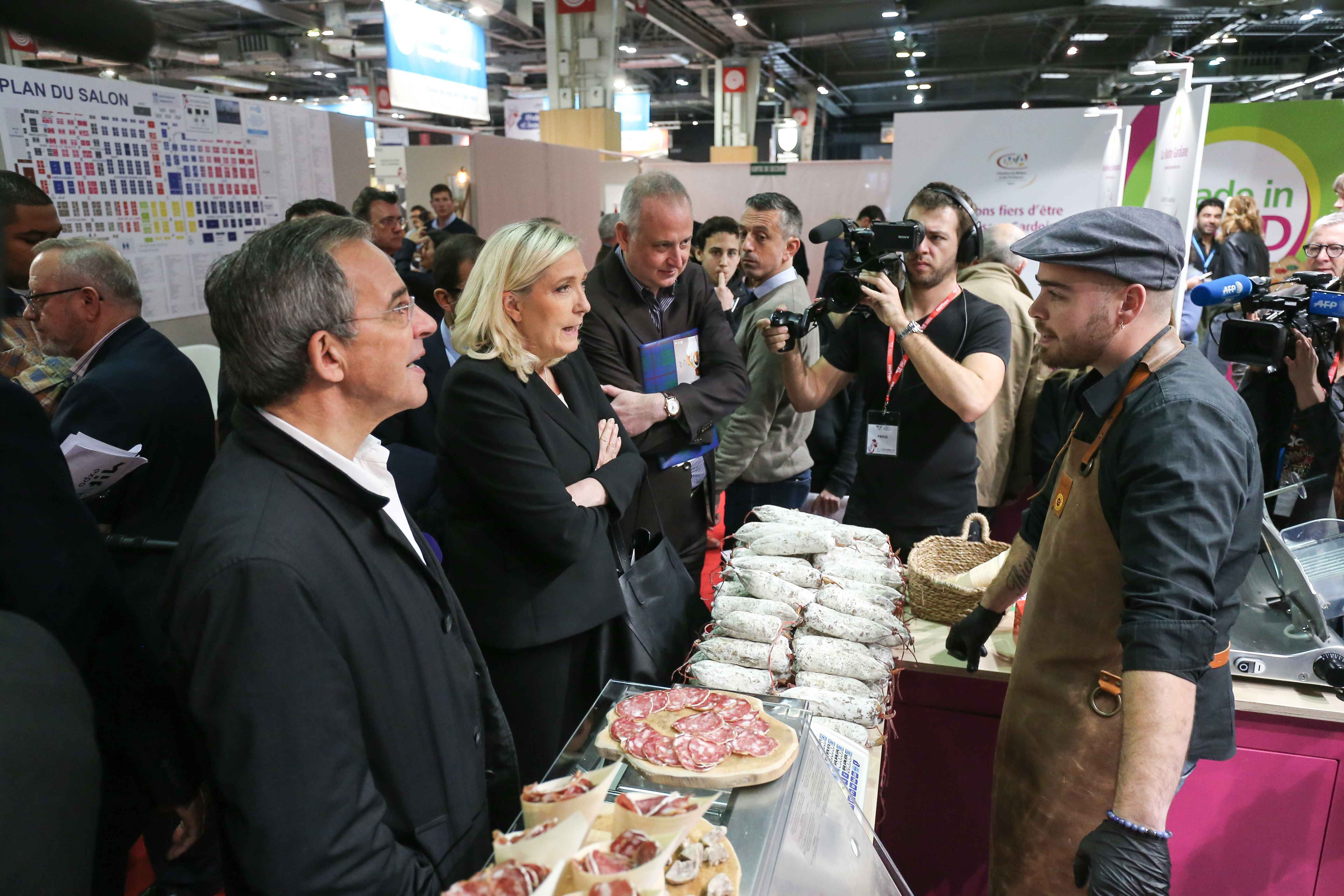 French far-right Rassemblement National (RN) party's president and MP Marine Le Pen (c) talks with a delicatessen maker as she visits the Made in France Fair, on November 9, 2019, at the Porte de Versailles, in Paris.