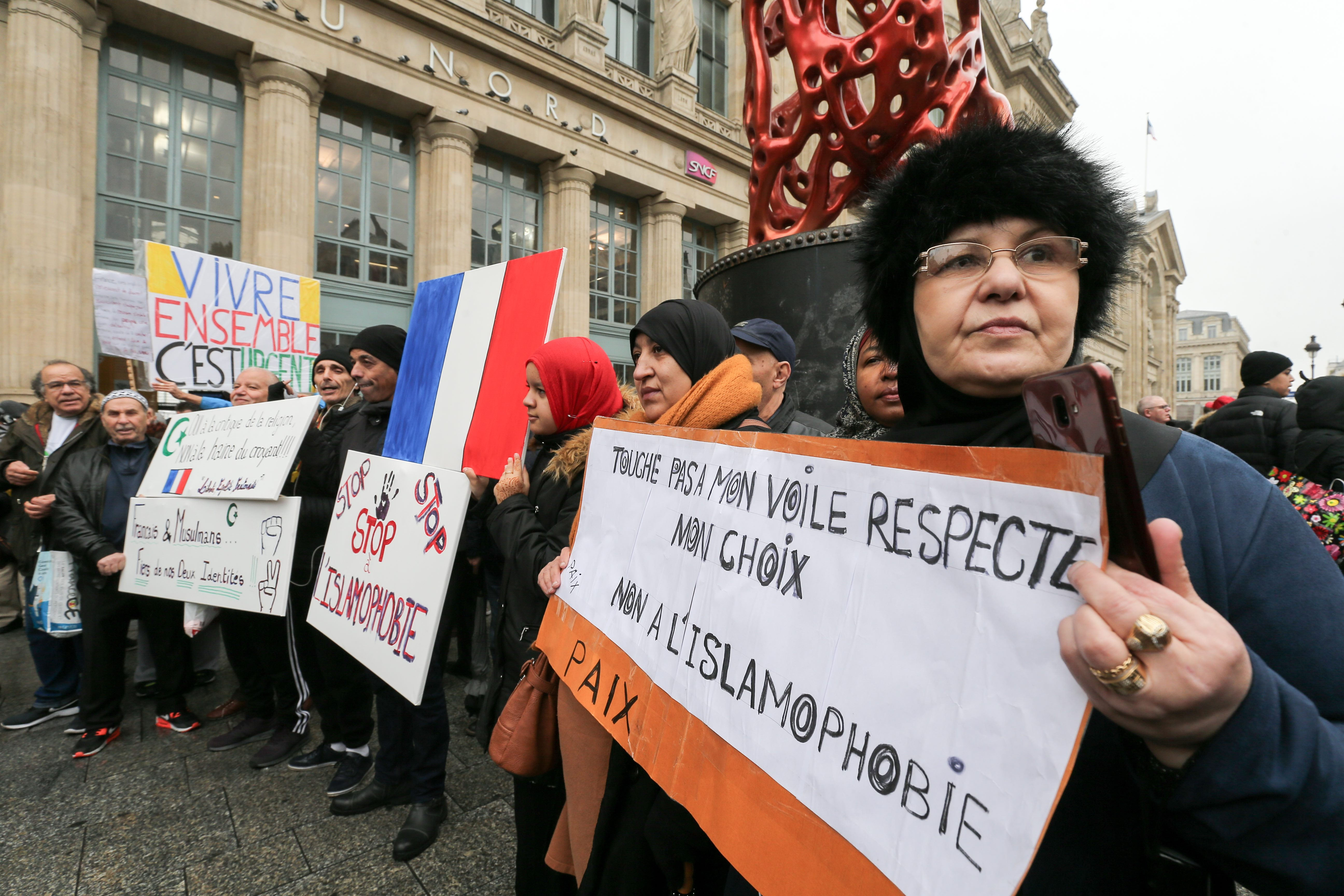 "Woman holds placard reading ""Don't touch my veil, respect my choice, no to Islamophobia » as she takes part in a march near the Gare du Nord, in Paris to protest against Islamophobia, on November 10, 2019."