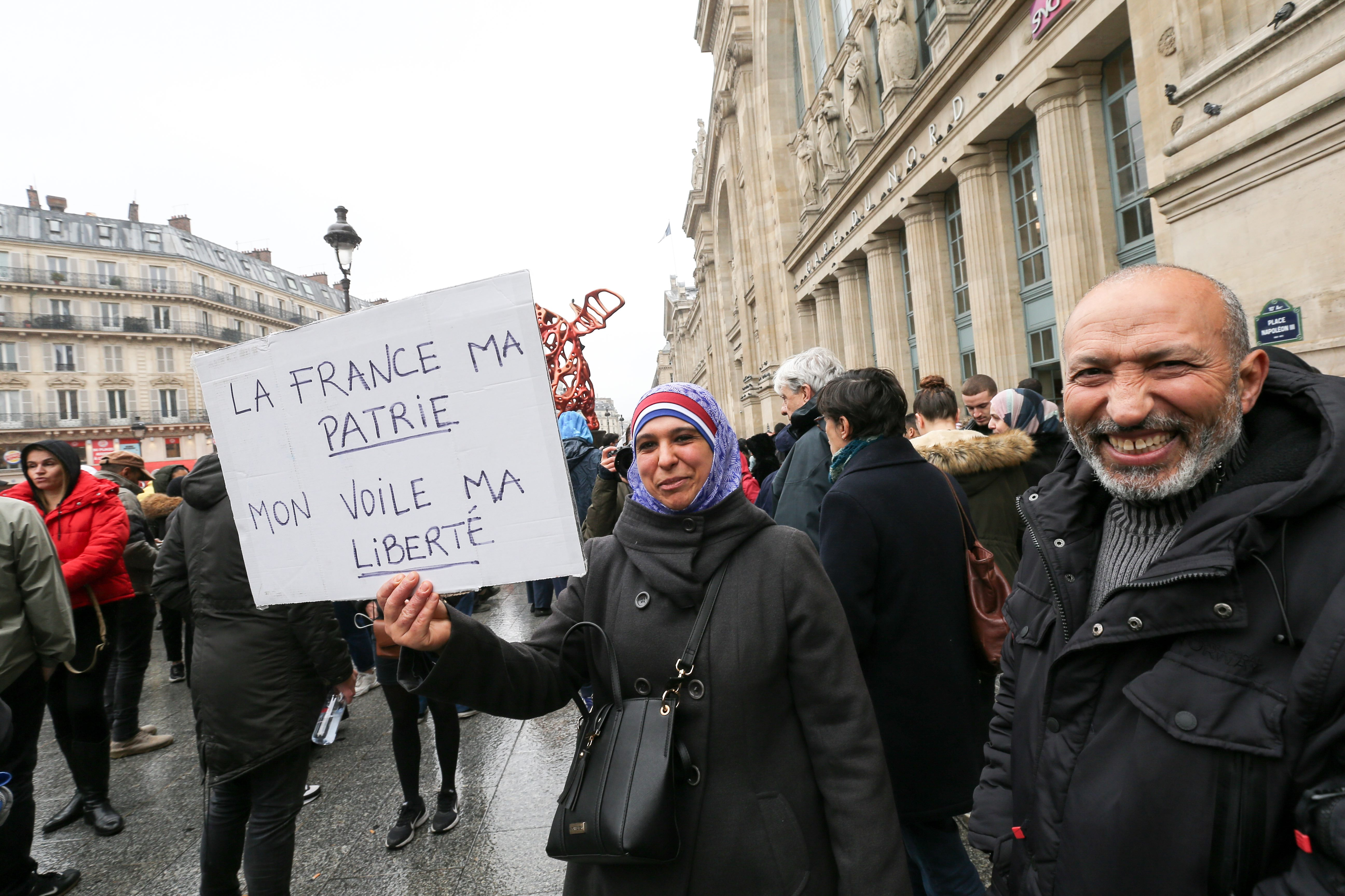 "Woman holds placard reading ""France, my country, my veil, my liberty » as she takes part in a march near the Gare du Nord, in Paris to protest against Islamophobia, on November 10, 2019."