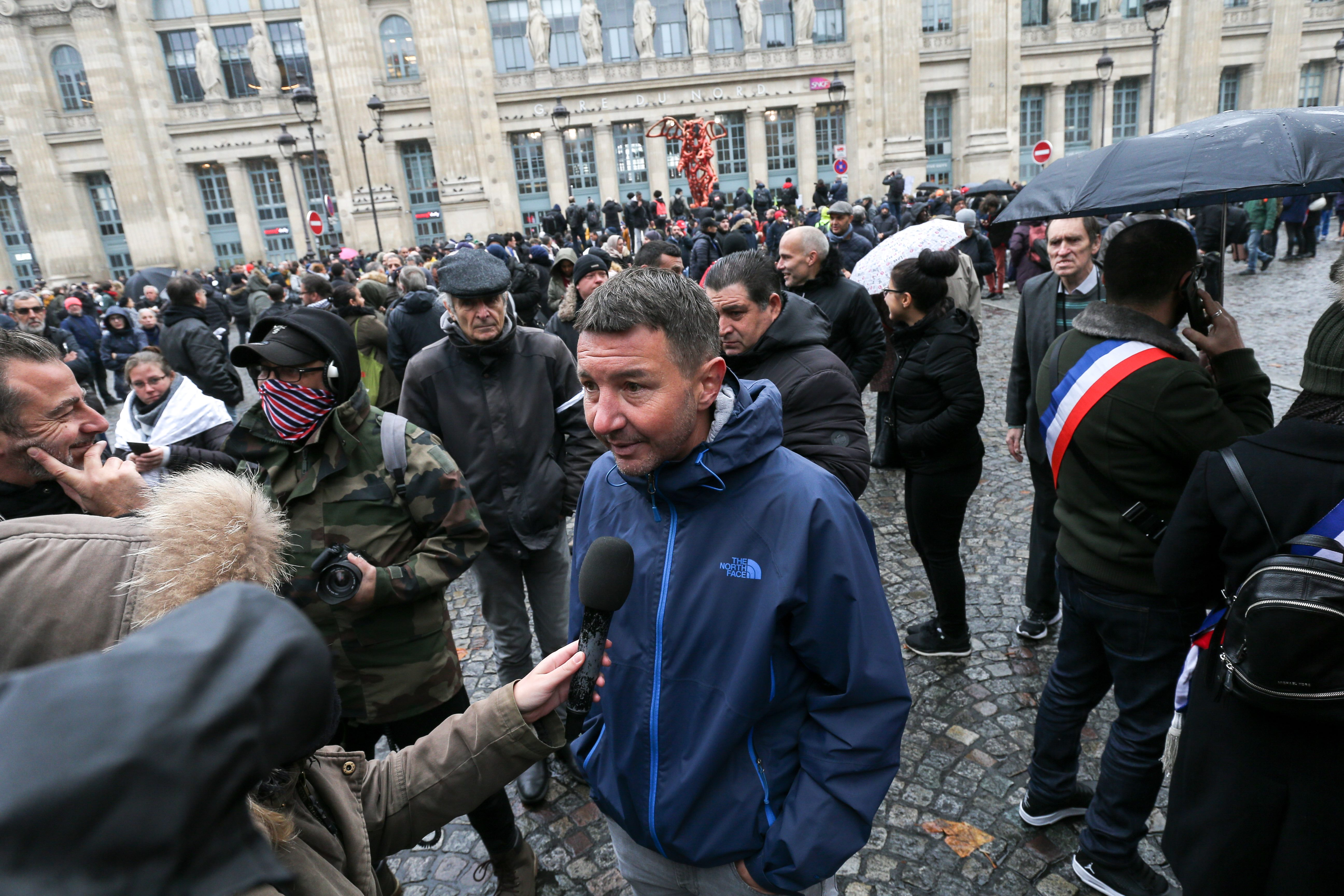 French far-left New Anti-Capitalist Party (NPA) member Olivier Besancenot (C) speaks with the press as she takes part in a march near the Gare du Nord, in Paris, on November 10, 2019, to protest against Islamophobia, at the call of several anti-racist acti