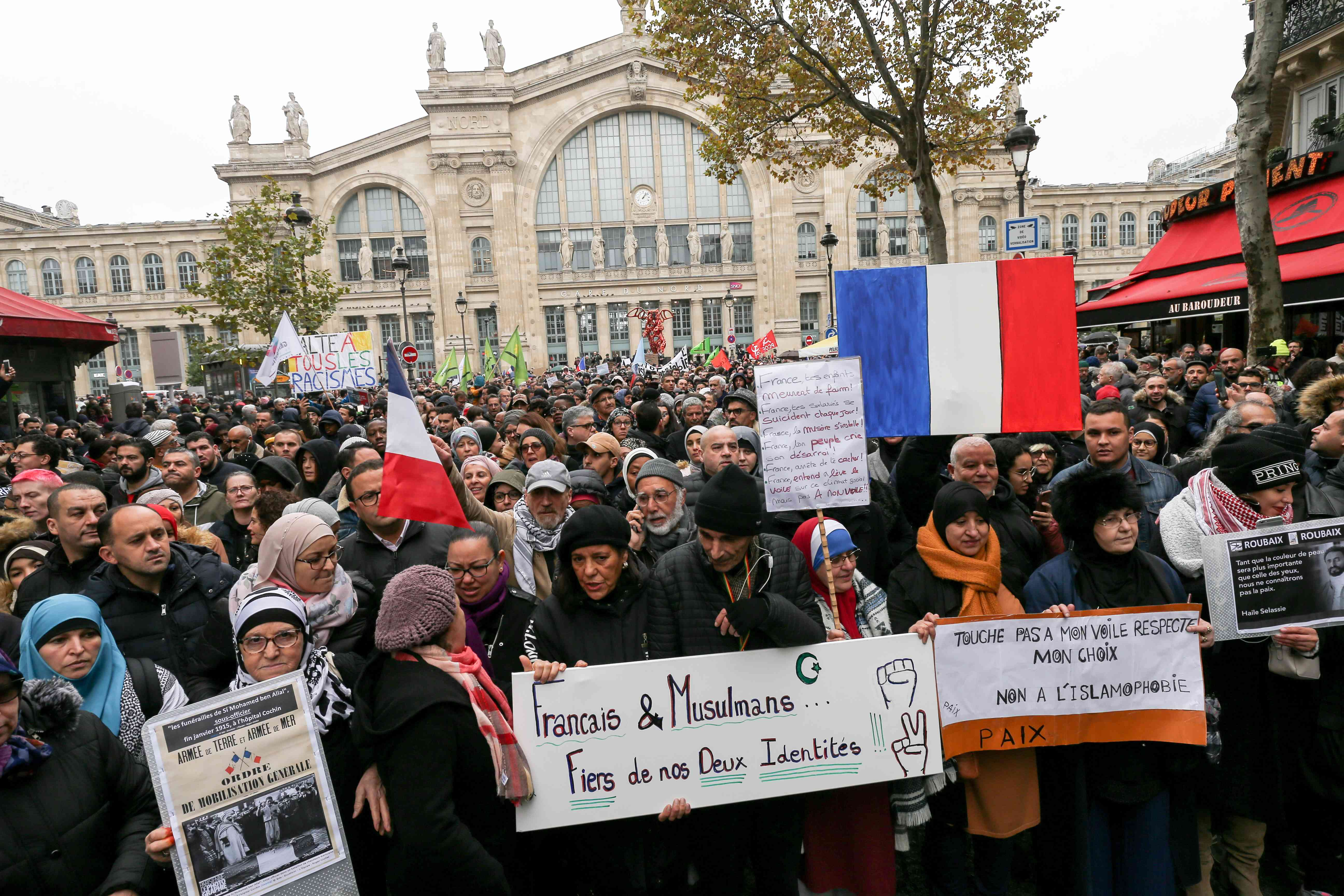 People wave French national flags, chant slogans and hold placards as they take part in a demonstration march in front of the Gare du Nord, in Paris, on November 10, 2019, to protest against Islamophobia, at the call of several anti-racist activists and co