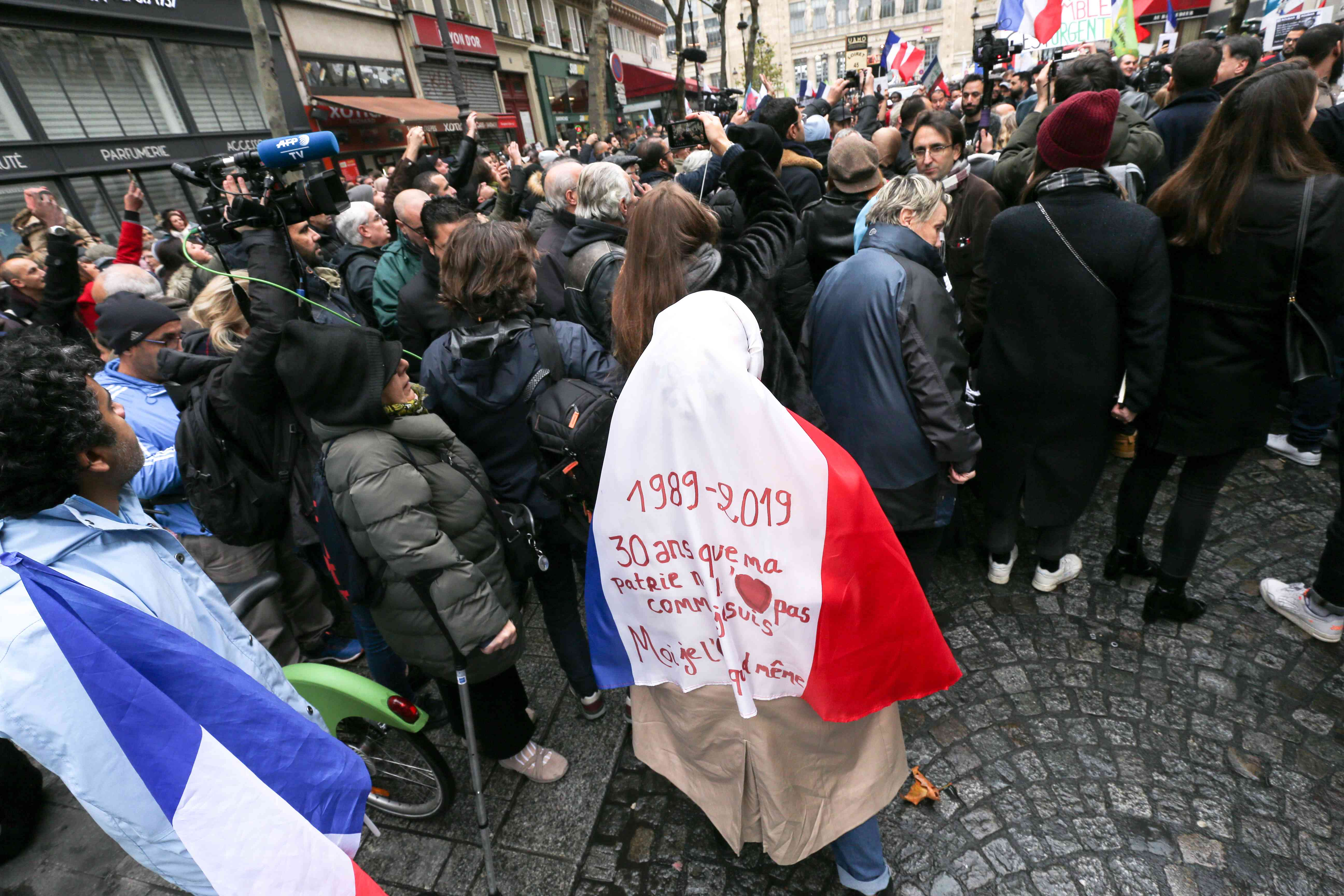 Woman is wearing a French national flag with inscription « 30 years that my country don't love me as I am, but I still love him » has she takes part in a march near the Gare du Nord, in Paris to protest against Islamophobia, on November 10, 2019.
