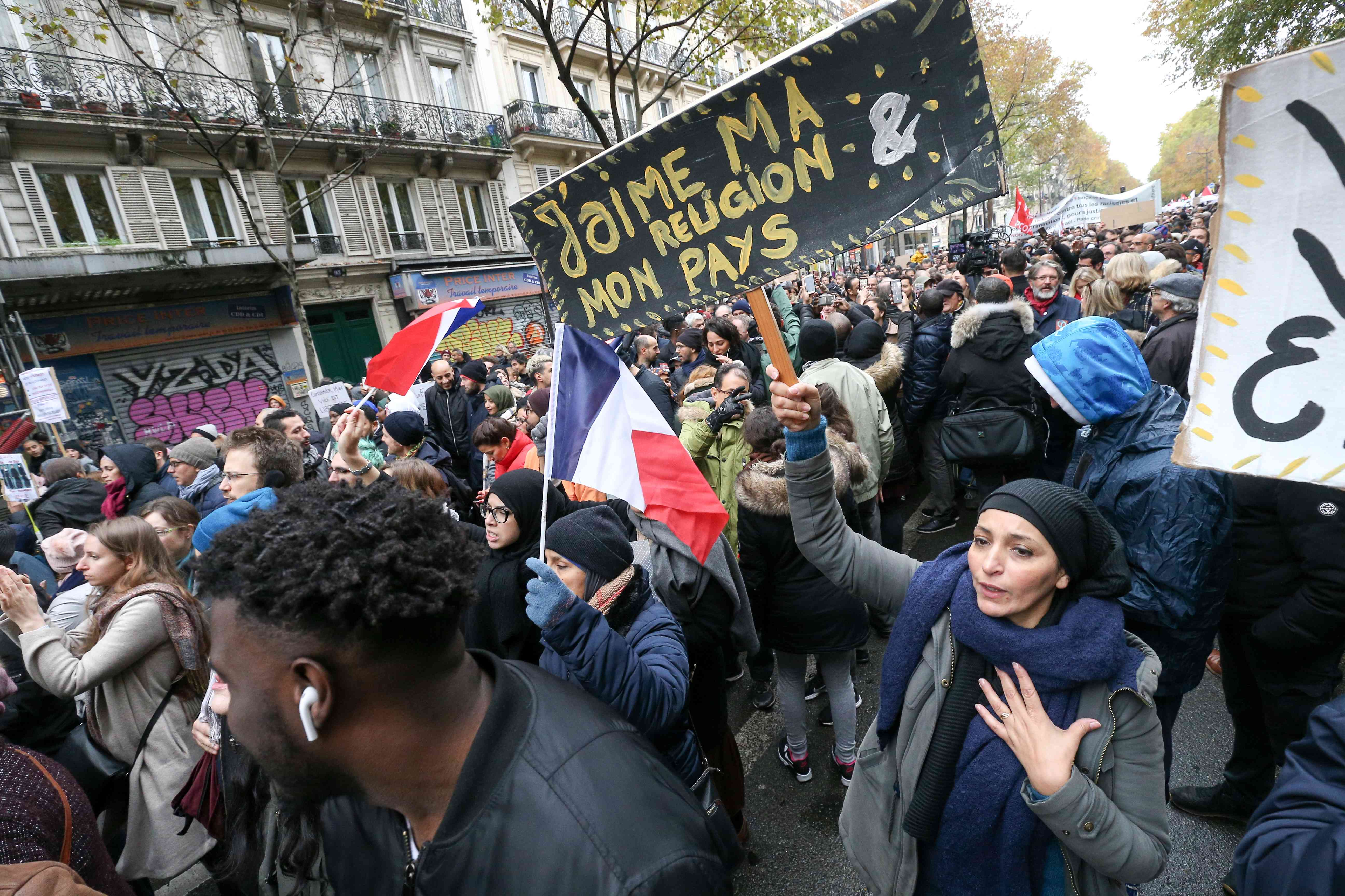 "Woman holds placard reading ""I love my religion, my country » has she takes part in a march near the Gare du Nord, in Paris to protest against Islamophobia, on November 10, 2019."