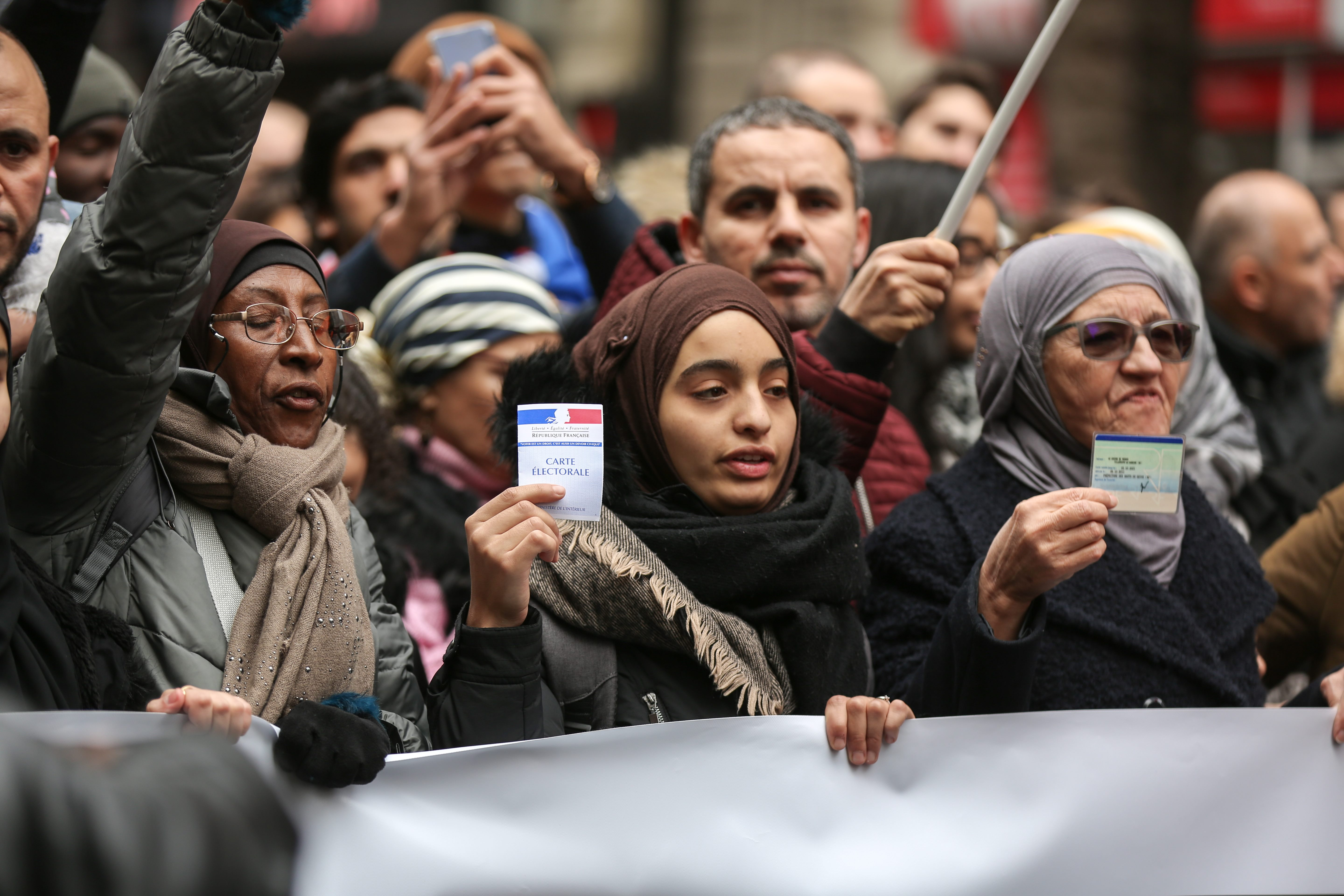 Two women show their French electoral card and ID card as they take part in a march near the Gare du Nord, in Paris, on November 10, 2019, to protest against Islamophobia, at the call of several anti-racist activists and collectives.