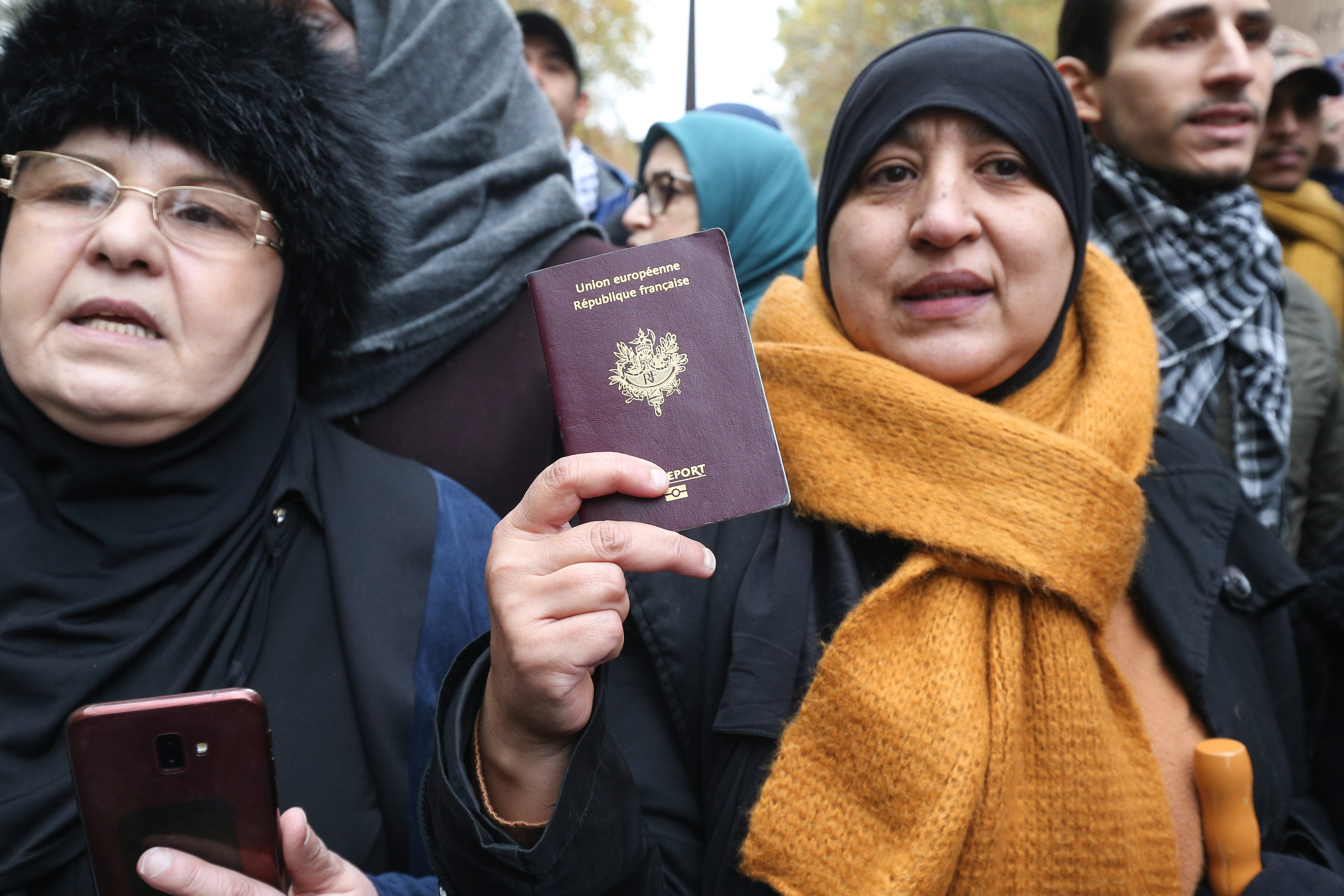 Woman show his French passport as she take part in a march near the Gare du Nord, in Paris, on November 10, 2019, to protest against Islamophobia, at the call of several anti-racist activists and collectives.