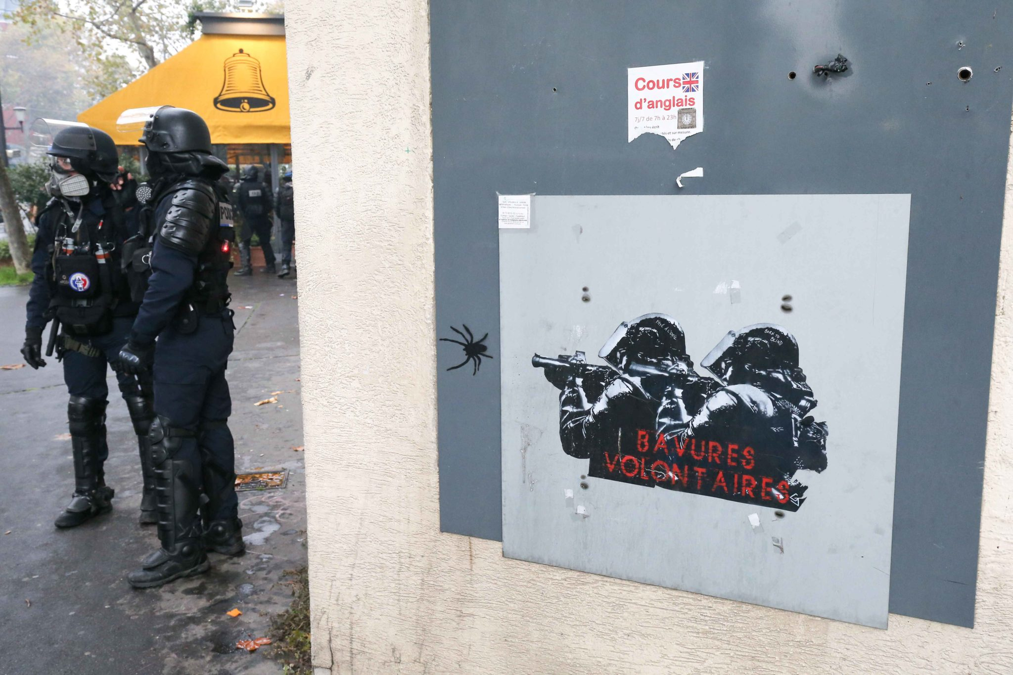 "Policemen are drawn on a wall with the text « volontary burrs » as French anti-riot policemen face members of the ""yellow vest"" (gilets jaunes) movement in Paris on November 16, 2019, during a demonstration marking the first anniversary of the ""yellow ve"