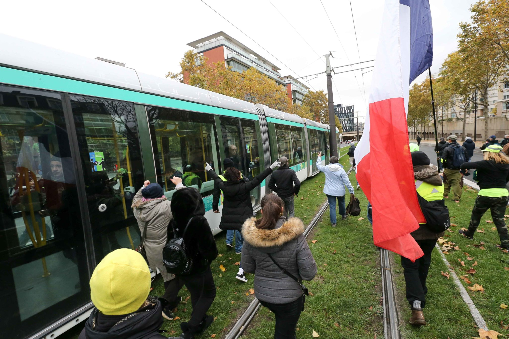 "Members of the ""yellow vest"" (gilets jaunes) movement block a tram in Paris on November 16, 2019, during a demonstration to celebrate the first anniversary of the movement. French ""yellow vest"" protesters are planning a series of nationwide demonstrations"
