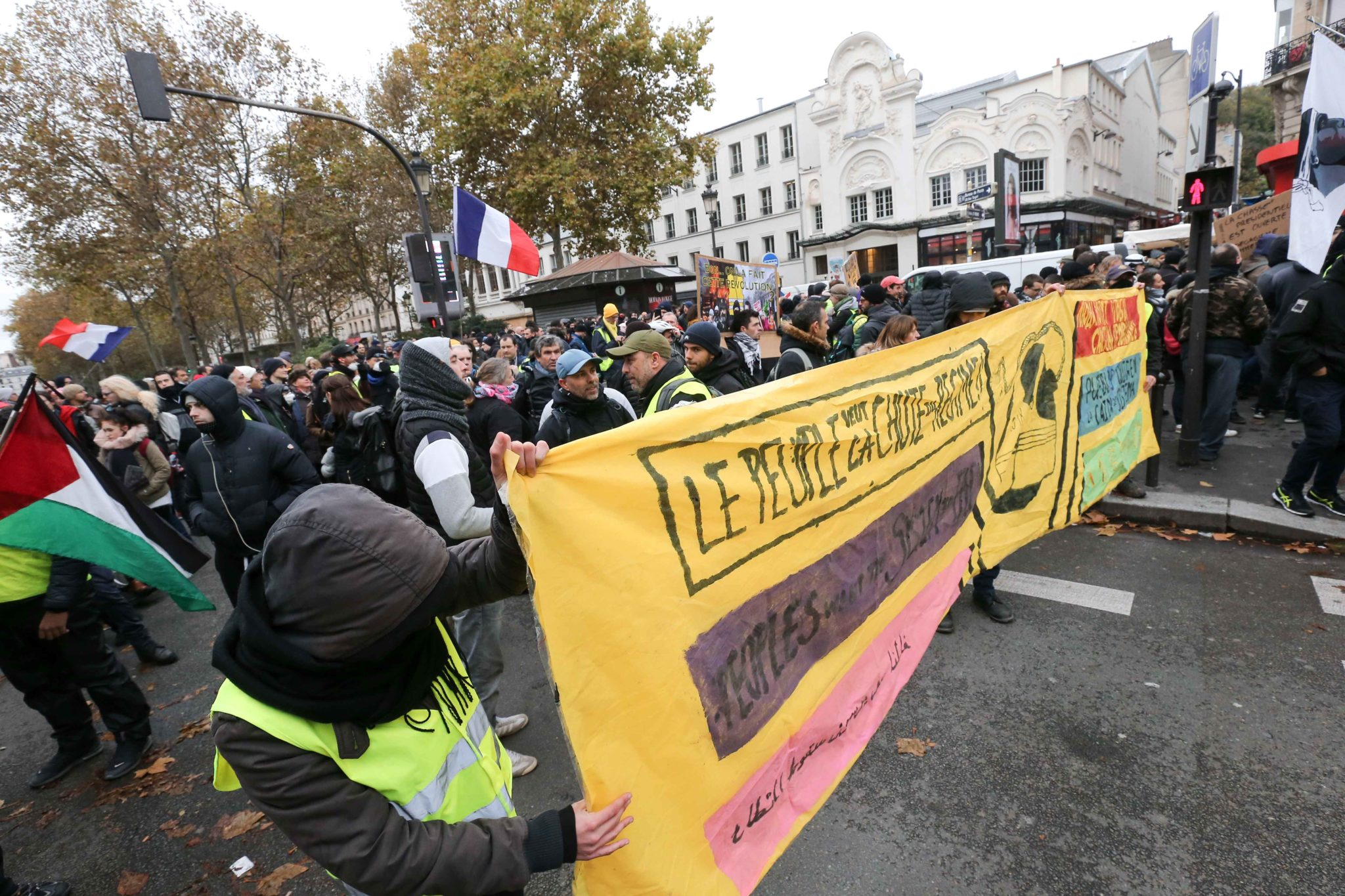 "Members of the ""yellow vest"" (gilets jaunes) movement hold a banner reading «The people want the fall of the regime» as they demonstrate in Paris on November 16, 2019, to celebrate the first anniversary of the movement. French ""yellow vest"" protesters ar"
