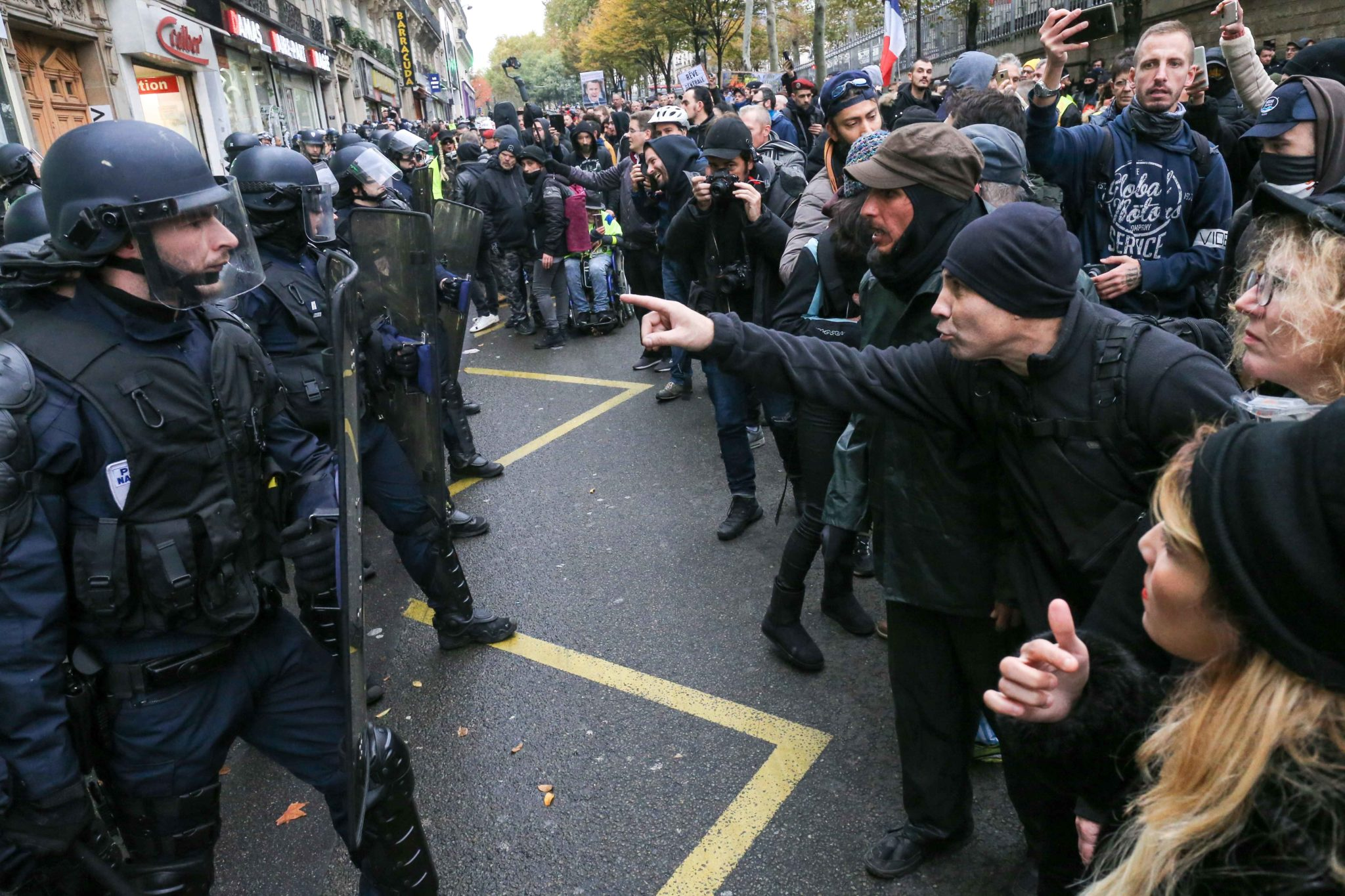 "French anti-riot policemen face protesters during a demonstration marking the first anniversary of the ""yellow vest"" (gilets jaunes) movement in Paris on November 16, 2019. French ""yellow vest"" protesters are planning a series of nationwide demonstrations"