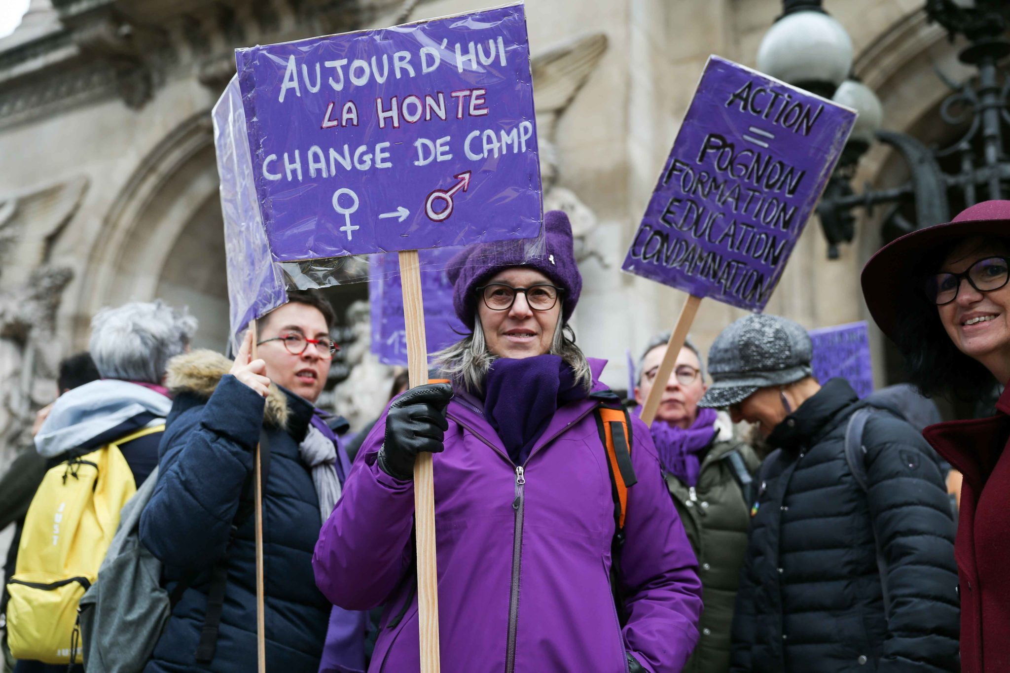 Women hold purple flags and signs during a protest to condemn violence against women, on November 23, 2019, in Paris, in front of the Garnier Opera House. Wearing purple – the adopted colour of feminist struggles – activists are taking to the streets o